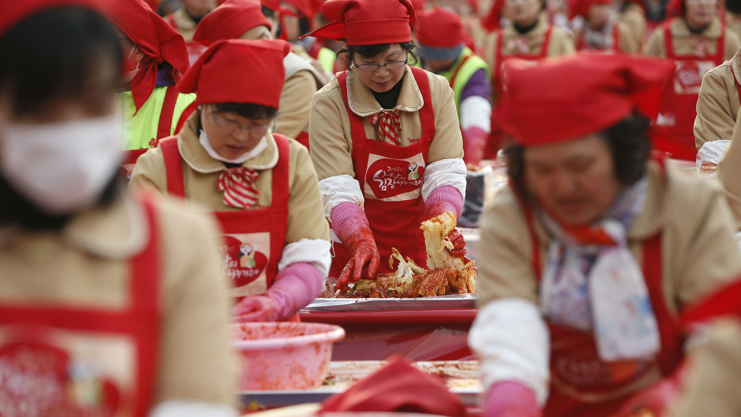 """Women make the traditional Korean side dish """"kimchi"""", or fermented cabbage, at a charity event at Seoul City Hall Plaza November 15, 2012. More than 2,000 volunteers made 270 tonnes of kimchi on Thursday to give away to needy people during the winter season. REUTERS/Kim Hong-Ji (SOUTH KOREA - Tags: FOOD SOCIETY)"""