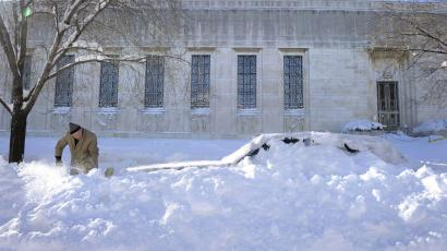 Eugene Wilson, 82, of Washington uses a broom to dig his Lincoln Towncar out of the snow in his Capitol Hill neighborhood of Washington, Sunday, Feb. 7, 2010, after it was buried by a blizzard that crippled the city.