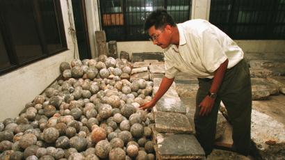 """Filipino Archeologist Dr. Eduardo Dizon examines hundreds of rounded granite stones as he segregates them for proper identification along with other granite slabs inside the National Museum in Manila Monday, Aug. 4, 1997 following its discovery last May from an ancient shipwreck off the contested islands of Spratlys in the south China Sea. The 18th Century find, made up of granite slabs, tombstones, and ball-like """"stone crushers"""" for mining, were believed to be part of artifacts being smuggled to Europe. (AP Photo/Bullit Marquez"""