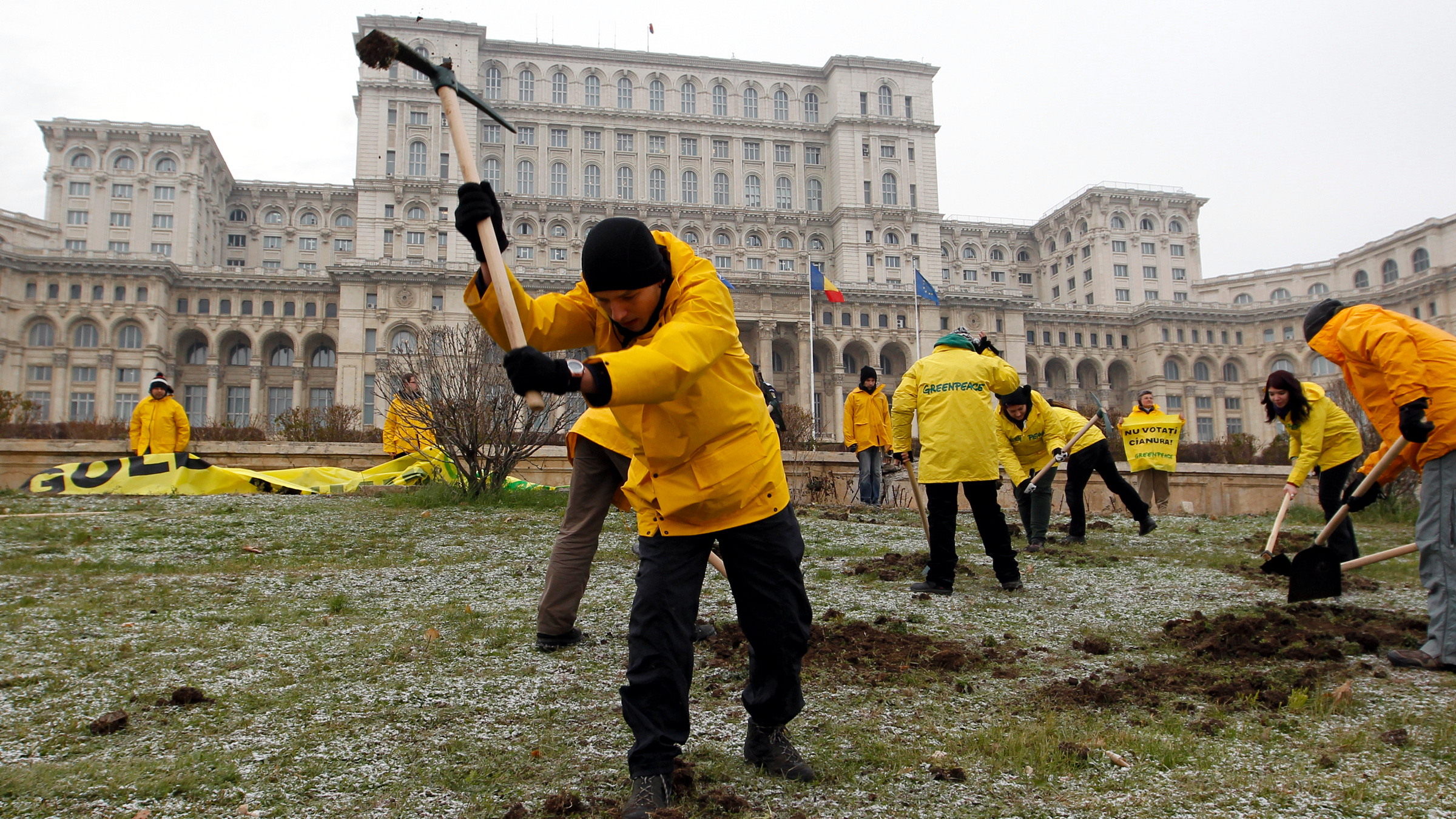 Greenpeace activists dig into the yard of Romania's Parliament, to protest against a Canadian company's plan to set up Europe's biggest open-cast gold mine in Romania, in Bucharest December 9, 2013. A special Romanian parliament commission overwhelmingly rejected a draft bill that would have allowed Canada's Gabriel Resources to set up Europe's biggest open-cast gold mine in the small Carpathian town of Rosia Montana last month. However, parliament plans to revise a mining law that could open way for the project.