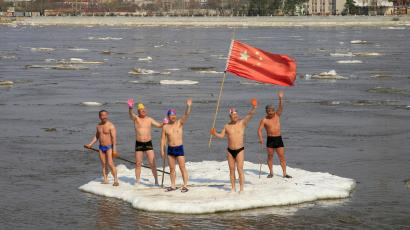 Winter swimmers wave on a piece of drifting ice with a Chinese national flag on the Amur River, in the Chinese border city of Heihe, Heilongjiang province May 6, 2013. REUTERS/China