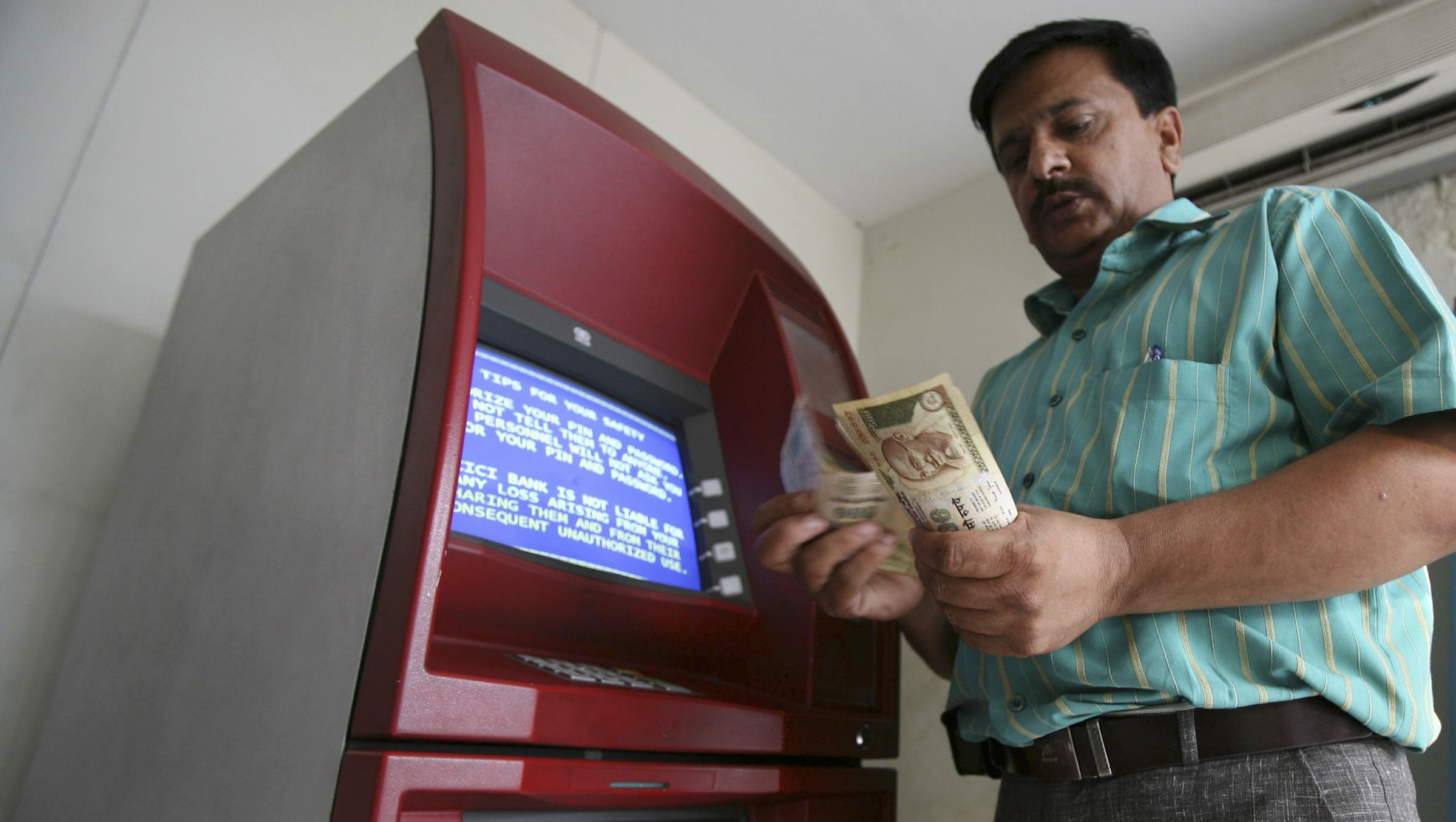 A man counts money after withdrawing it from an ATM in Jammu October 14, 2008. Indian shares held gains of 1.5 percent on Tuesday, led by Reliance Industries, but investors were circumspect and watchful after a sharp rebound this week on concerted action across the world to rescue the financial sector. REUTERS/Amit Gupta (INDIAN-ADMINISTERED KASHMIR) - RTX9J5C