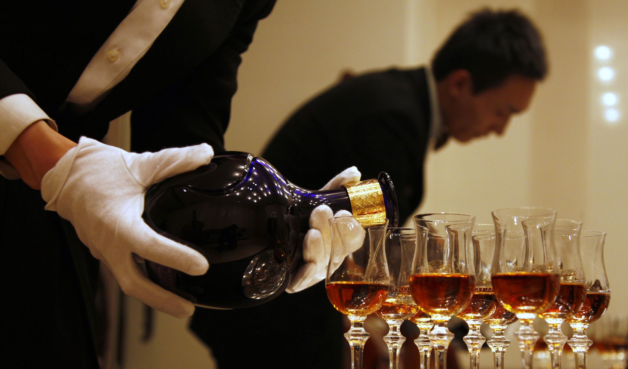 A waiter is reflected in a mirror as he pours Scotch whisky from luxury brand Royal Salute into glasses at a launch ceremony for the release of the '62 Gun Salute' series in central Beijing December 6, 2010. The luxury whisky is selling at 15,000 yuan ($2,260) per bottle, with the launch consisting of a 'British Royal banquet' where 62 guests will fire 62 guns.      REUTERS/David Gray    (CHINA - Tags: SOCIETY) - RTXVGCO