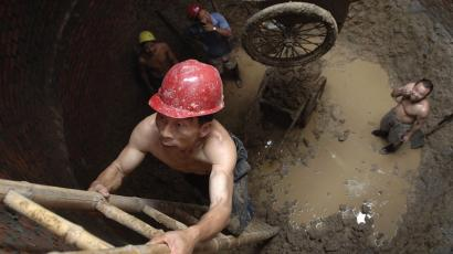Labourers work in a sewage pipe on a hot day in Hefei, east China's Anhui province August 9, 2007. Temperatures in eight of 10 major cities across China were above their long-term averages in July, data from the China Meteorological Administration showed. REUTERS/Jianan Yu