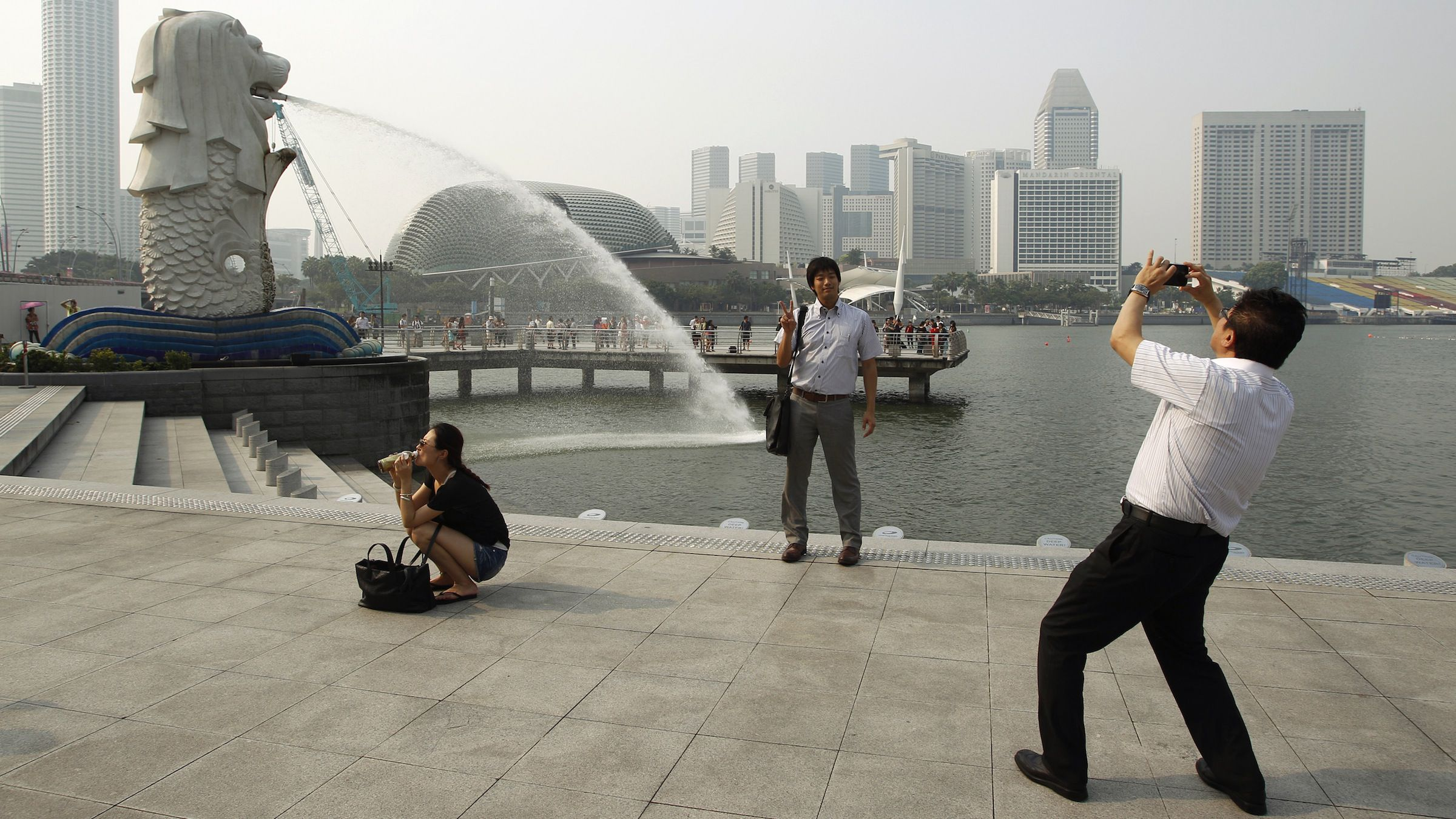 Tourists take photos of the Merlion in the hazy skyline of Singapore June 18, 2013. Air pollution in Singapore and Malaysia rose to unhealthy levels on Monday thanks to illegal forest clearing in Indonesia, prompting Singapore to advise people against staying outdoors for long and to urge Indonesia to do something to stop it.  REUTERS/Edgar Su (SINGAPORE - Tags: ENVIRONMENT TRAVEL) - RTX10RTH
