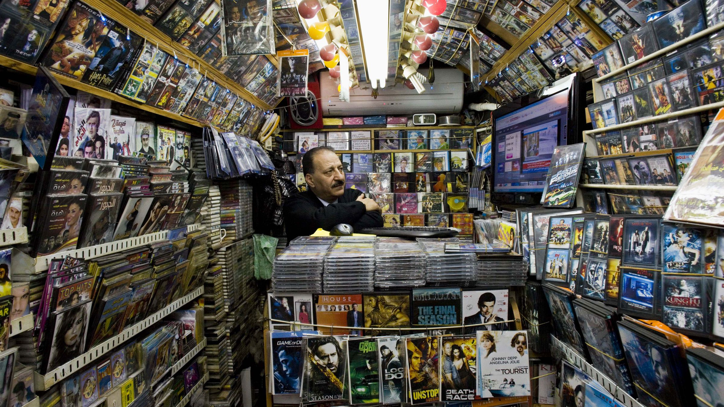 A Palestinian watches news from Egypt on television inside his shop in Jerusalem's Old City, Thursday, Feb. 3, 2011.