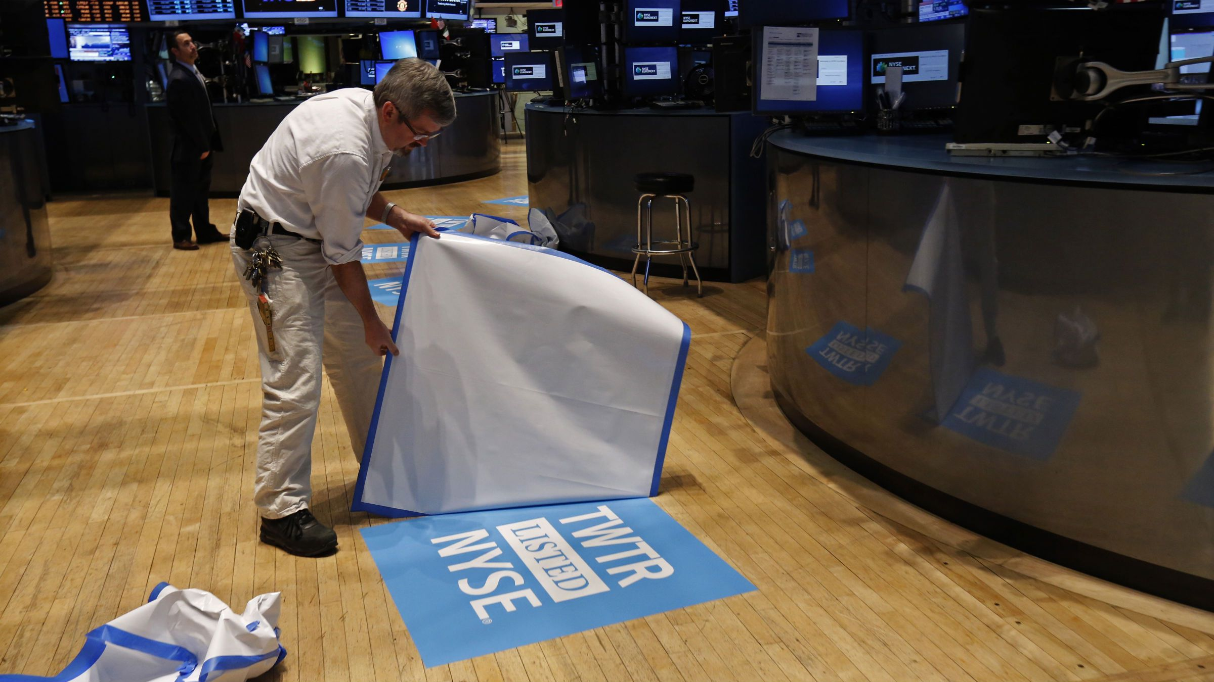 A worker reveals the Twitter listing on the floor before the company's IPO at the New York Stock Exchange in New York, November 7, 2013.