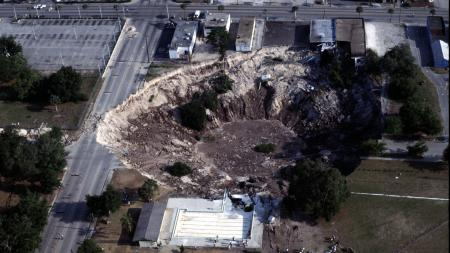 This aerial view shows the large sinkhole that continues to grow as workers try unsuccessfully to retrieve sunken sports cars from the depression in Winter Park, Fla., May 11, 1981. (AP Photo