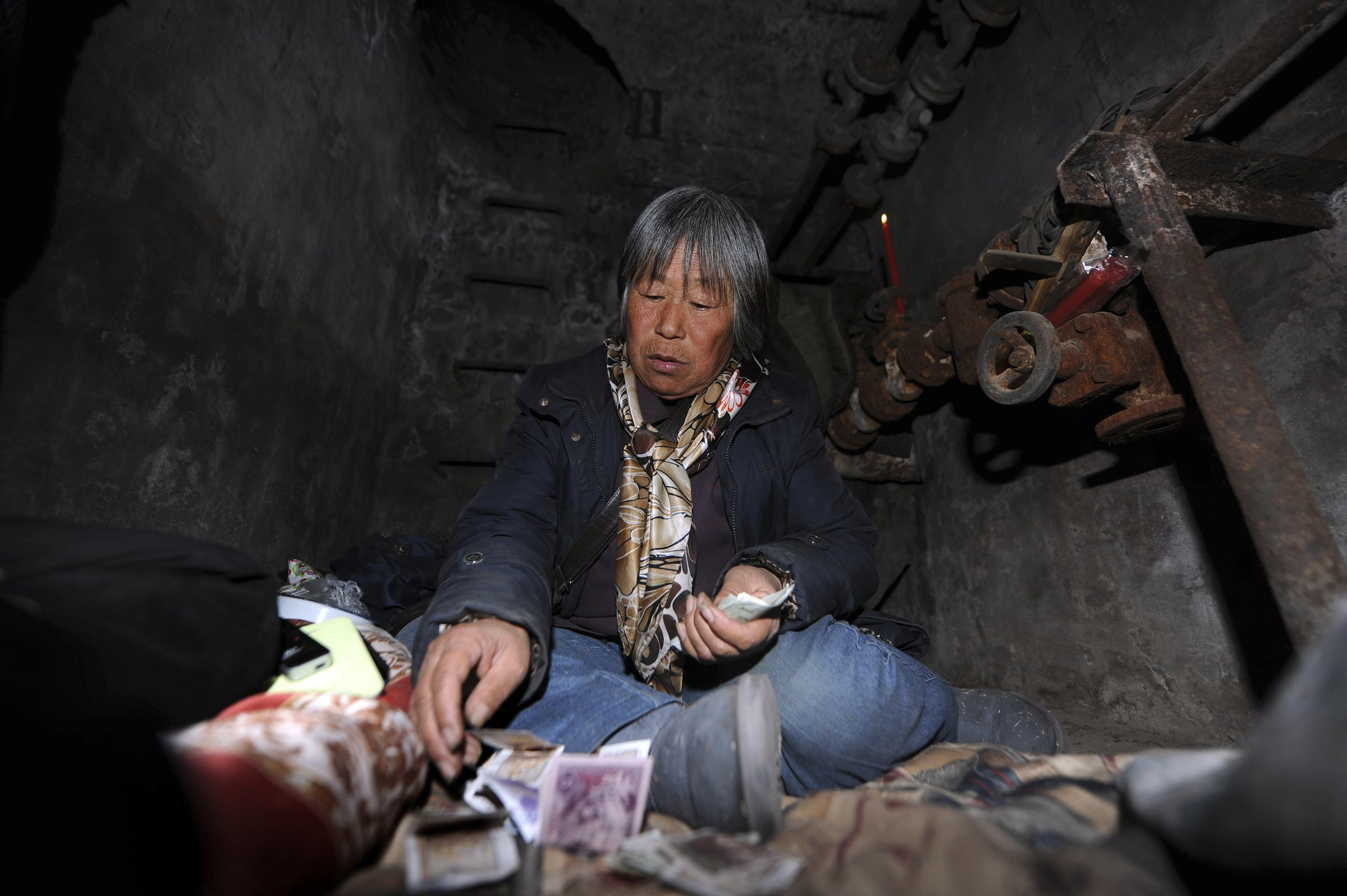 Quan Youzhi, 66, counts money in her dwelling inside an underground shaft in Beijing, December 5, 2013. According to local media, around five underground shafts, in which people were living in, were blocked by city officials on Friday morning at a neighbourhood in Beijing. One of the dwellers, Quan Youzhi, 66, has been living in the shafts, which were originally used for the city's heating system, for around 20 years as she could not afford to pay rent for housing after she came to Beijing, and has since relocated several times after being chased away by law enforcement officials. Quan supports herself with about 10 yuan ($1.64) daily, which she makes from collecting waste bottles. Picture taken December 5, 2013.