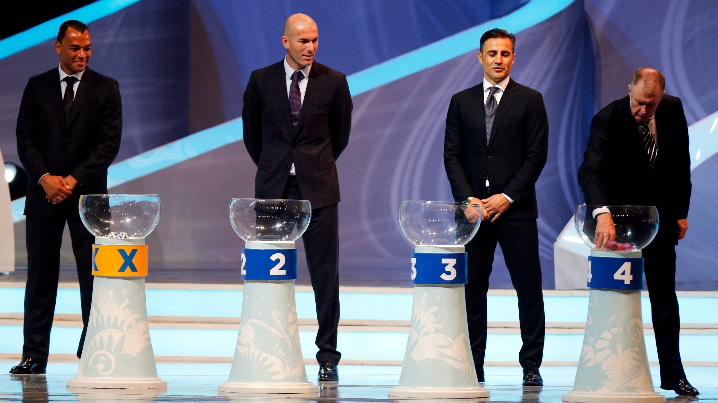 Former England soccer player Geoff Hurst (R) draws a ball from a pot as former Brazil player Cafu (L), former France player Zinedine Zidane (2nd L) and former Italy player Fabio Cannavaro look on during the draw for the 2014 World Cup at the Costa do Sauipe resort in Sao Joao da Mata, Bahia state, December 6, 2013. The 2014 World Cup finals will be held in Brazil from June 12 through July 13.