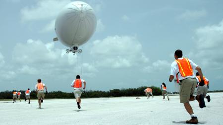 Handlers from the Airship Management Services race toward a Skyship 600 blimp as it prepares to touch down at Naval Air Station Key West, Florida in this handout photo provided by the U.S. Navy and taken on June 27, 2008. Helium, known for making the voice squeaky after it is inhaled from party balloons, but it is also a vital element in industries from aerospace and defence, to smart phones and flat-screen TVs, medical equipment and deep-sea diving tanks. The U.S. Federal Helium Reserve has been providing around a third of global crude helium and 40 percent of U.S. supply. But this will be turned off after October 7 unless Congress acts to extend its life. Picture taken June 27, 2008.