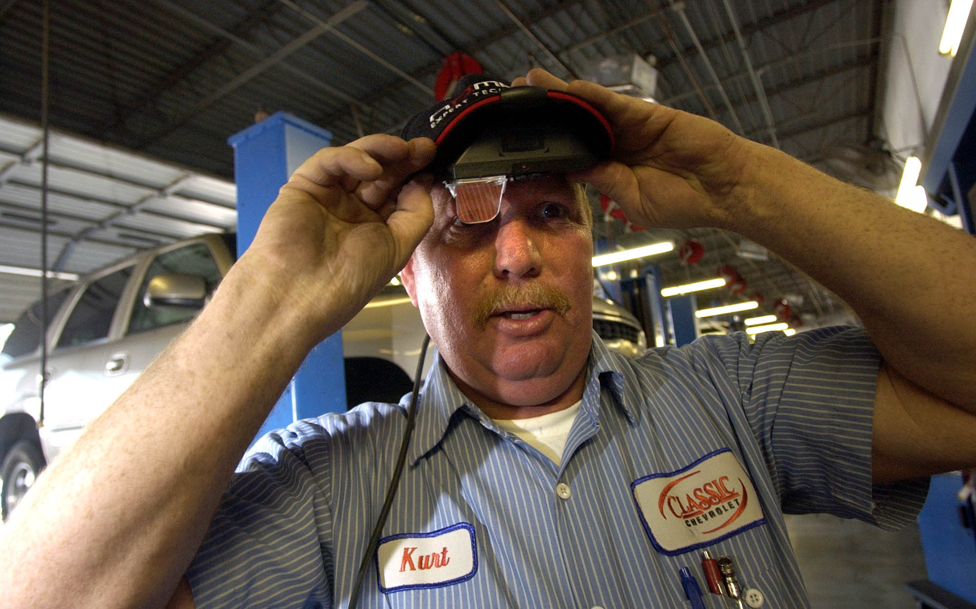 ** ADVANCE FOR MONDAY SEPT. 20 ** Auto mechanic Kurt Ward demonstrates a wearable computer over his right eye that is used to read on line repair manuals in Grapevine, Texas, Friday, Sept. 3, 2004. The wearable computer includes a wireless Internet connection, that allows him to read from manufacturers' online auto-repair manuals. (AP Photo/L.M. Otero)