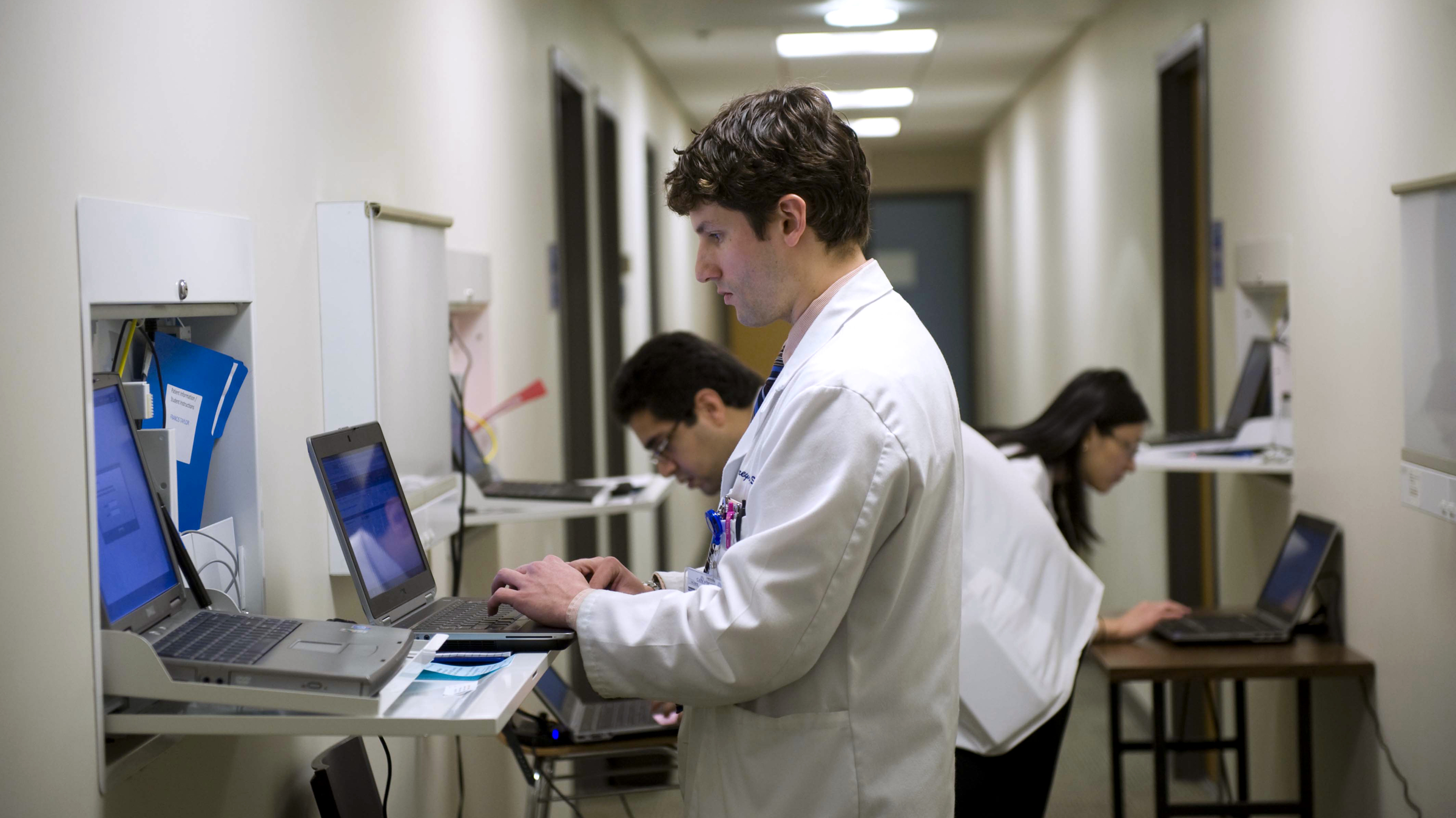 Gregory Shumer, center, Omer Shah, left, and Jasmine Zheng, all third-year Georgetown medical students, prepare to meet with a patient/actor in an exam room on the Georgetown Medical School campus in Washington, Friday, March 16, 2012.  The students were learning how to better integrate the computer in the exam room without losing the human touch. As the nation moves to paperless medicine, doctors are grappling with an awkward challenge: How do they tap the promise of computers, smartphones and iPads in the exam room without losing the human connection with their patients? Are the gadgets a boon, or a distraction? (AP Photo/Kevin Wolf)