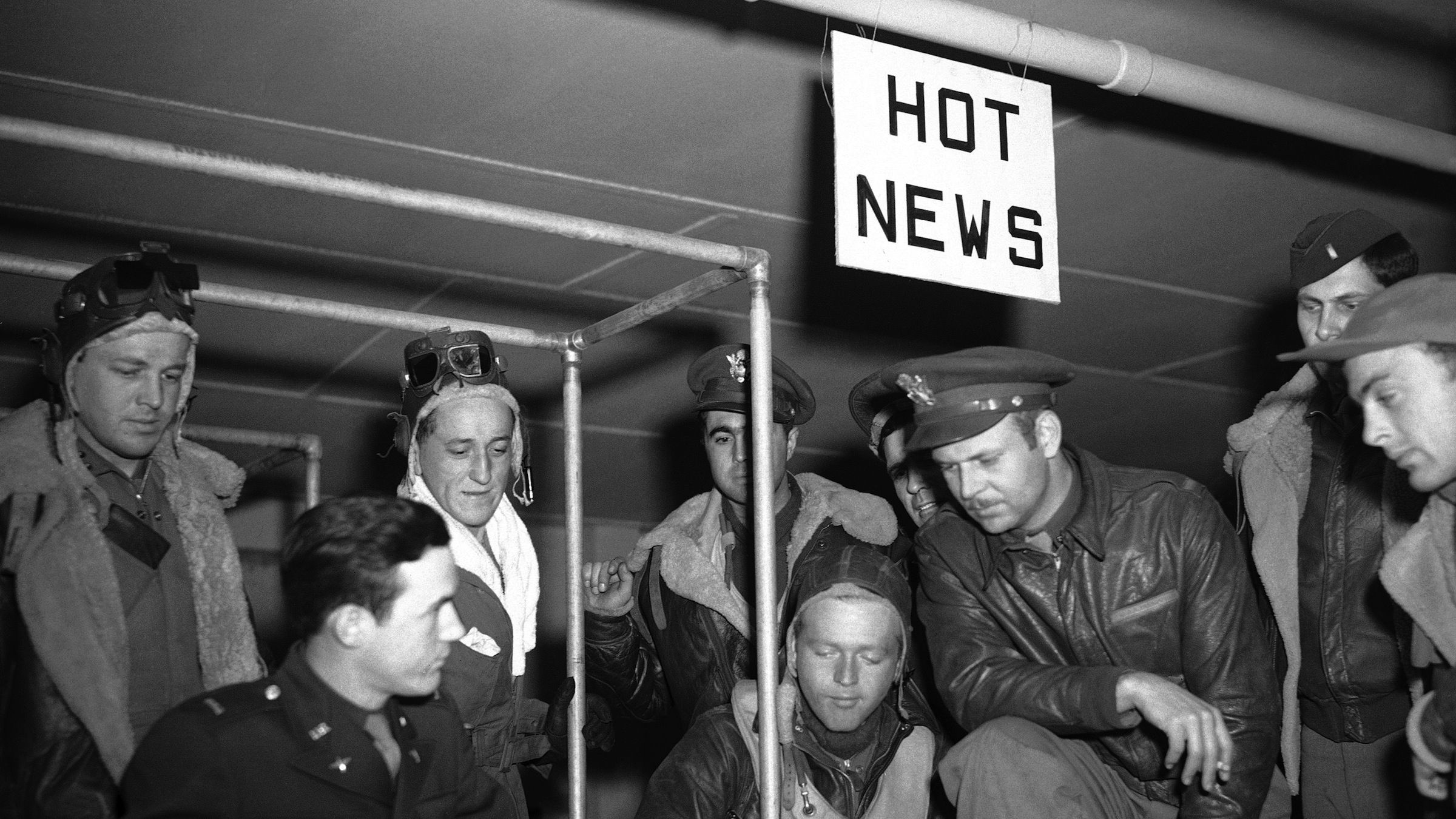 Lieutenant Roger Moran of Hornell, N.Y., (seated, in helmet) talks to intelligence officers at the ìhot newsî table in England on August 6, 1943. Standing, with arm on knee, is Lt. Curtis Burgan of Hoisington, Kan. At this table hot news, in the form of new type of enemy fighter or flak encountered, is reported immediately ñ forming a possible addition.  (AP Photo)