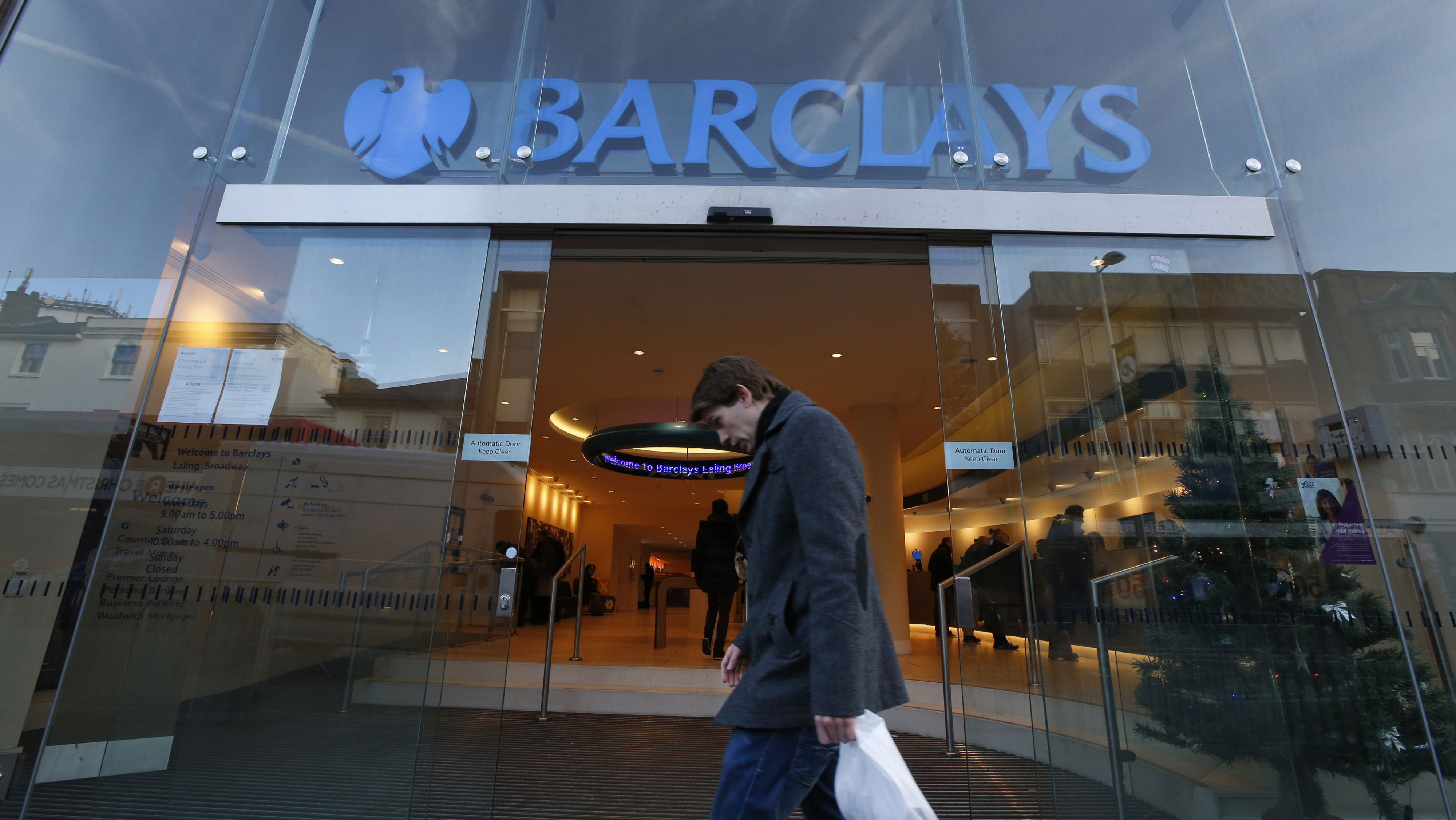 A man walks past a Barclays Bank branch in London, Wednesday, Dec. 4, 2013. The European Commission has fined a group of major global banks a total of 1.7 billion euros (2.3 billion US dollars) for colluding to profit from the interest rates market. The banks are accused of manipulating for years European and Japanese benchmark interest rates that affect hundreds of billions of dollars in contracts globally, from mortgages to credit card bills.The banks named as participating in cartels were Barclays, Deutsche Bank, Royal Bank of Scotland, Societe Generale, Credit Agricole, HSBC, JPMorgan, UBS and Citigroup. Barclays escaped fines because it was the bank that notified the commission of the cartel's existence, while JPMorgan, HSBC and Credit Agricole have as yet not settled. (AP Photo/Lefteris Pitarakis)