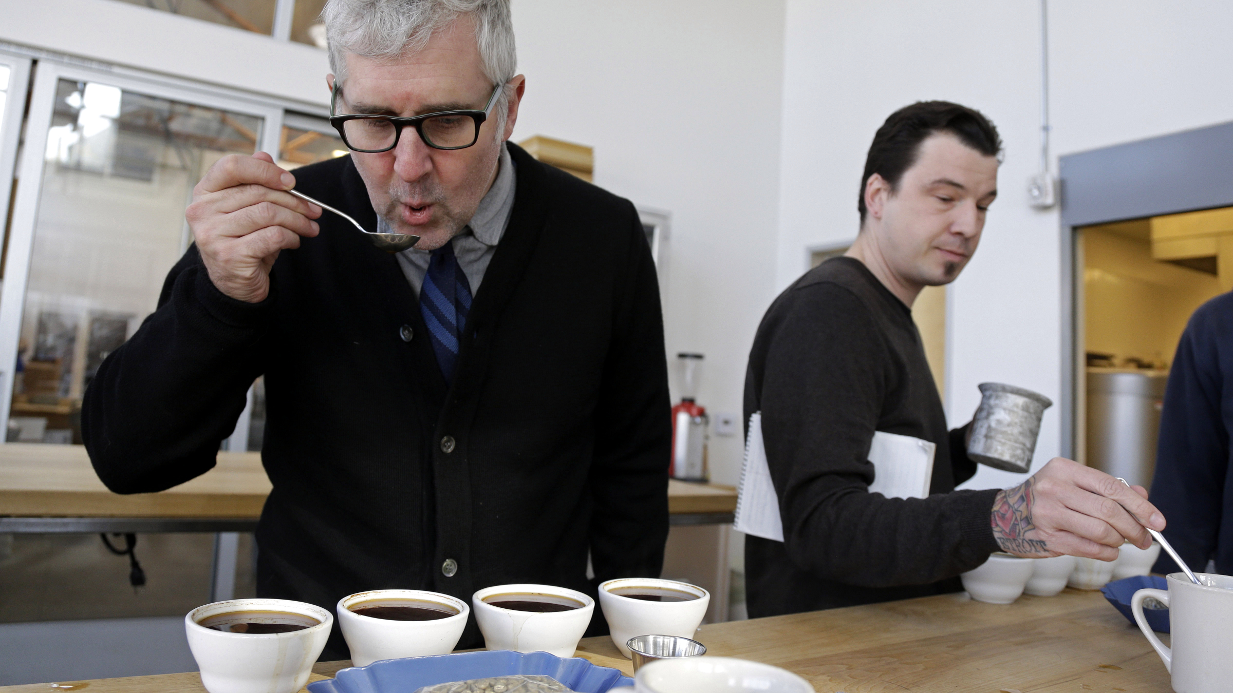 In this photo taken Thursday, Jan. 3, 2013, James Freeman, left, founder of Blue Bottle Coffee cups coffee samples, observing the tastes and aromas of brewed coffee from Uganda at his roastery in Oakland, Calif.