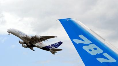 The vertical stabilizer of a Boeing 787 Dreamliner is seen as an Airbus A380, the world's largest jetliner, takes off during the 49th Paris Air Show at the Le Bourget airport near Paris June 23, 2011.