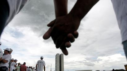 Brazilian farmers hold hands to form a circle in the Esplanade of Ministries while demonstrating in favor of the modifications in the Forestry Law that are being debated in Congress, in Brasilia April 5, 2011. Farmers are hoping that the changes will include a softening of the law's requirements for farmers to keep a certain percentage of their land forested.