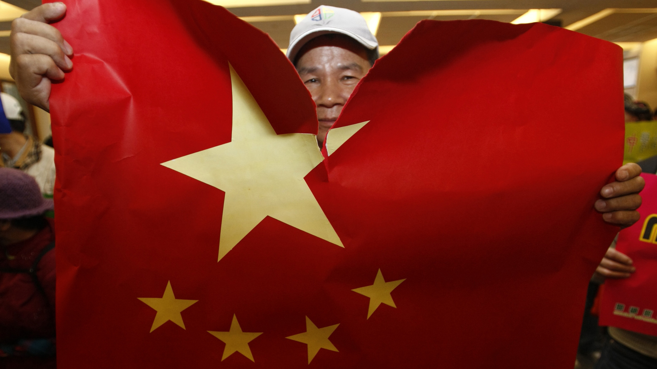 A protester tears a China flag during Chairman of China's Association for Relations Across the Taiwan Straits (ARATS) Chen Yunlin's visit to the Taiwan National Museum before cross straits meetings in Taipei December 20, 2010. Taiwan and China are planning to sign a medical agreement to share information on epidemics and cooperate in developing new drugs. REUTERS/Pichi Chuang