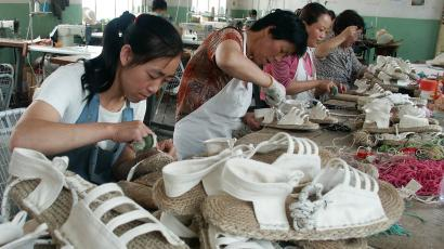 Chinese workers make flax shoes at a footwear export company in Gangu county of Tianshui, northwest China's Gansu Province, June 21, 2005. The EU's executive arm said this month that imports of six categories of Chinese footwear in the first four months of 2005 had jumped 681 percent from a year earlier, with shipments of some shoes soaring more than 1,000 percent. Prices dropped by 28 percent over the same period. Picture taken June 21, 2005. CHINA OUT REUTERS/China Newsphoto