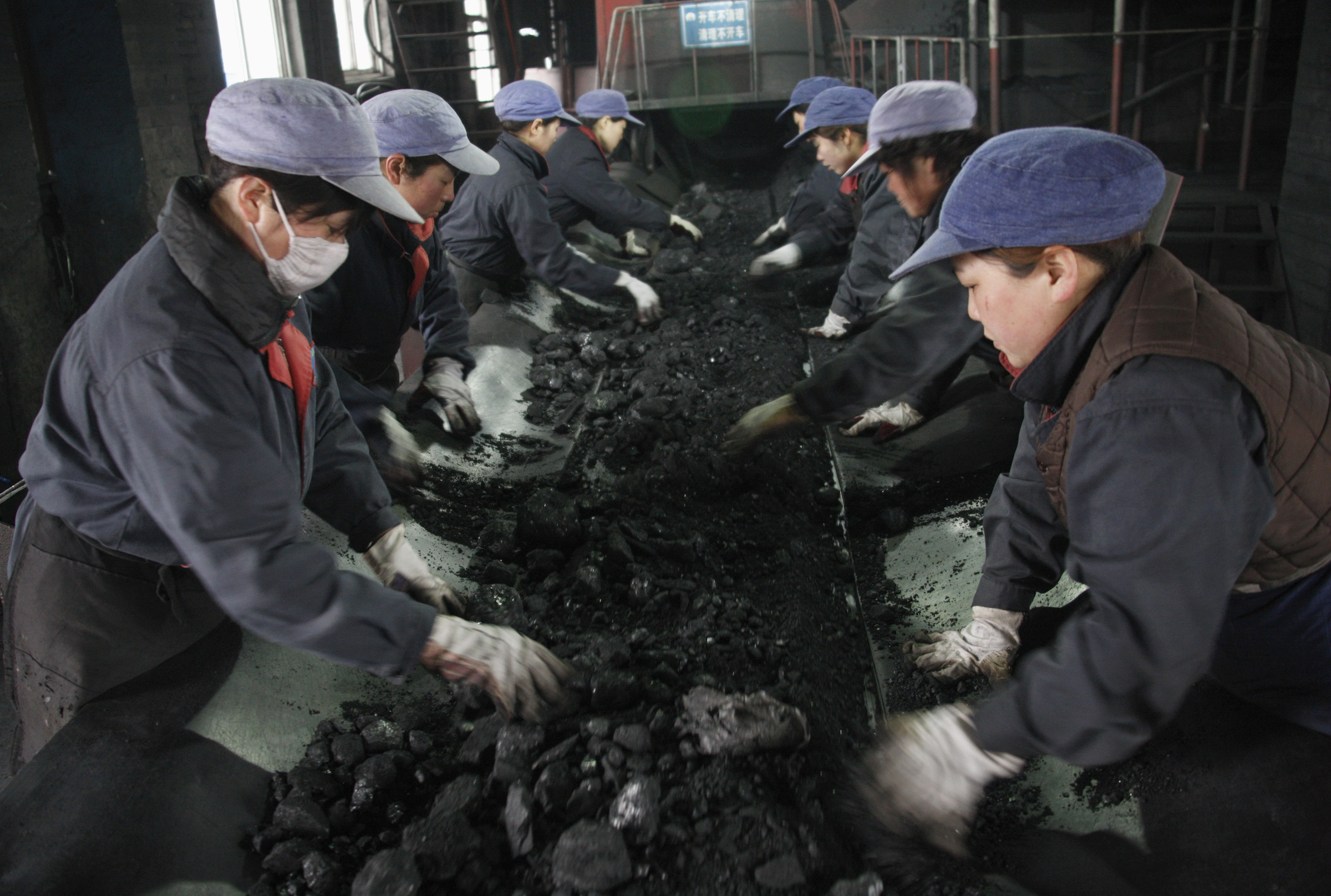 Labourers filter out stones from cinder at a workshop of a coal mine's coal washery in Huaibei, Anhui province March 8, 2010. This year China is targeting national coal output of 3.15 billion tonnes, a 3.3 percent increase, the country's economic planning ministry, the National Development and Reform Commmission, said in its annual economic plan on March 5.  REUTERS/Stringer (CHINA - Tags: ENERGY BUSINESS) CHINA OUT. NO COMMERCIAL OR EDITORIAL SALES IN CHINA - RTR2BDP6
