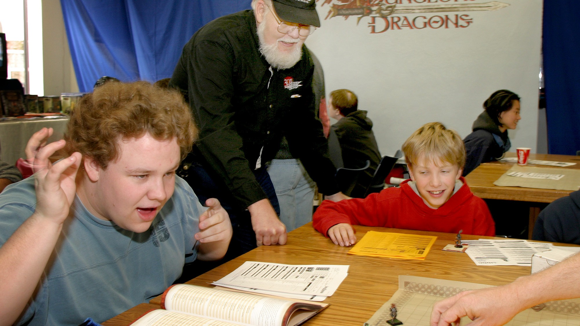 Taylor Babcock, left, reacts after a roll of dice while playing Dungeons & Dragons in Falcon Heights, Minn. with the game's creator Dave Arneson, center, and Alex Mears-Freeman, right,  Saturday  Oct. 16, 2004. The role playing game marked it's 30th anniversary with games played by fans around the world.(AP Photo/Andy King)