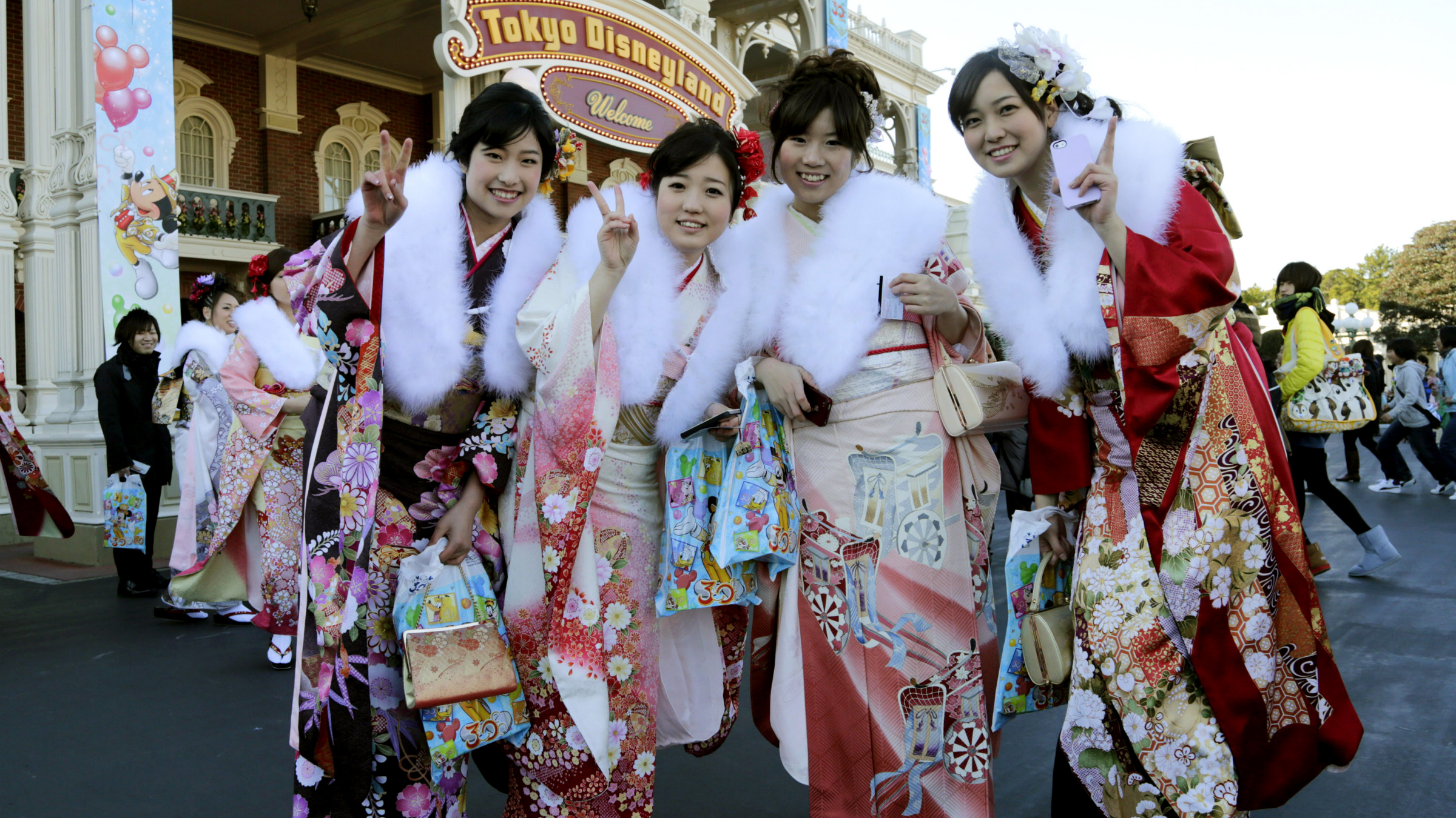 Japanese women dressed in kimonos, who will turn 20-years-old this year, pose for photographers after attending a Coming of Age ceremony at Tokyo Disneyland at Urayasu, near Tokyo, Monday, Jan. 13, 2014. (AP Photo/Shizuo Kambayashi)