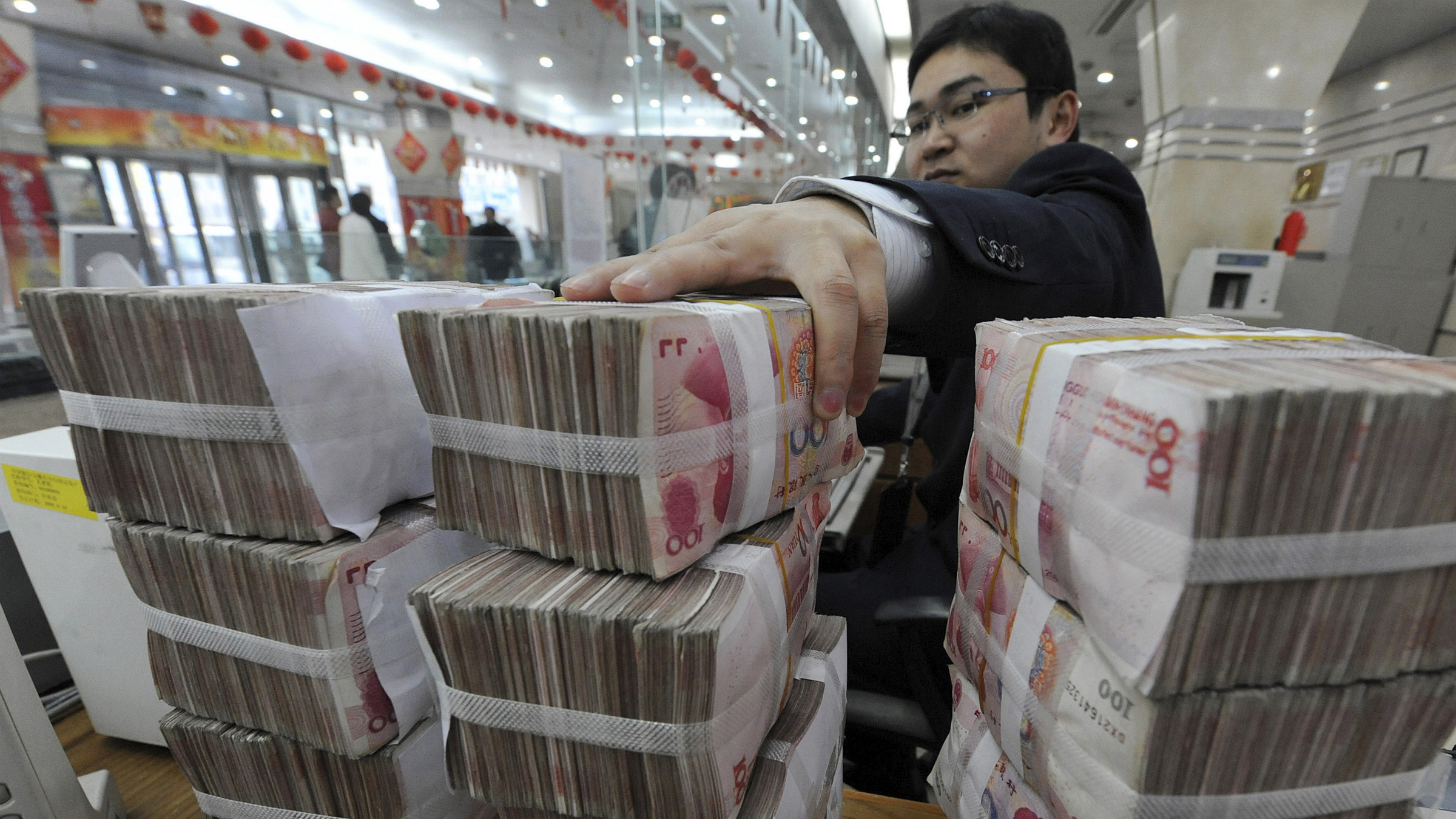 An employee counts Chinese yuan banknotes at a Bank of China branch in Hefei, Anhui province March 10, 2010. Chinese banks extended about 700 billion yuan ($102.5 billion) in new loans in February, half that of January, as the government clampdown on lending took hold, state media said on Wednesday. REUTERS/Stringer