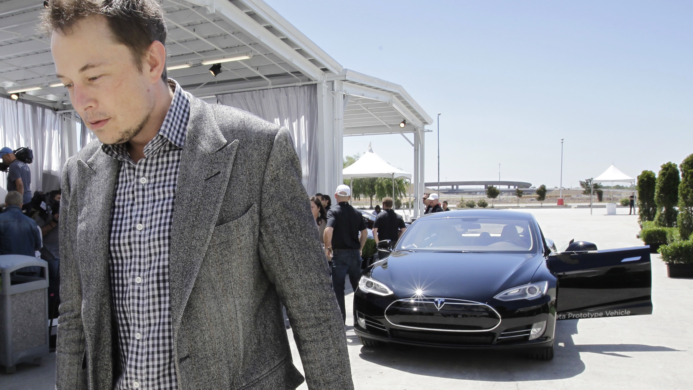 Tesla CEO Elon Musk walks past the Tesla Model S after a news conference at the Tesla factory in Fremont, Calif., Friday, June 22, 2012. The first Model S sedan car will be rolling off the assembly line on Friday.  (AP Photo/Paul Sakuma)