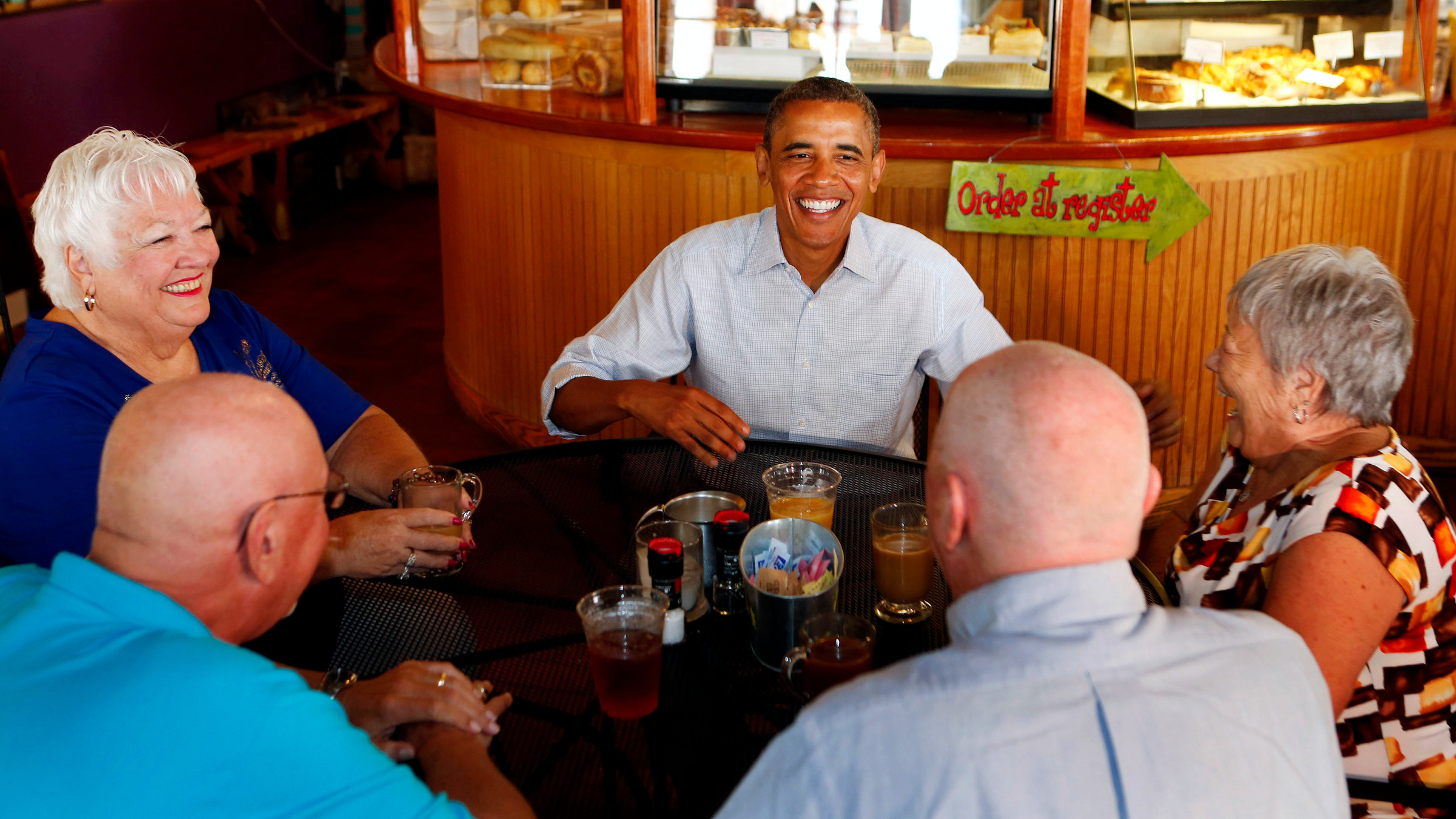 U.S. President Barack Obama eats with senior citizens inside the Ossorio Bakery and Cafe while campaigning in Cocoa, Florida, September 9, 2012. From L-R are: Jan Clark, Jerry Clark, Obama, John Hill, and Shirley Hill.