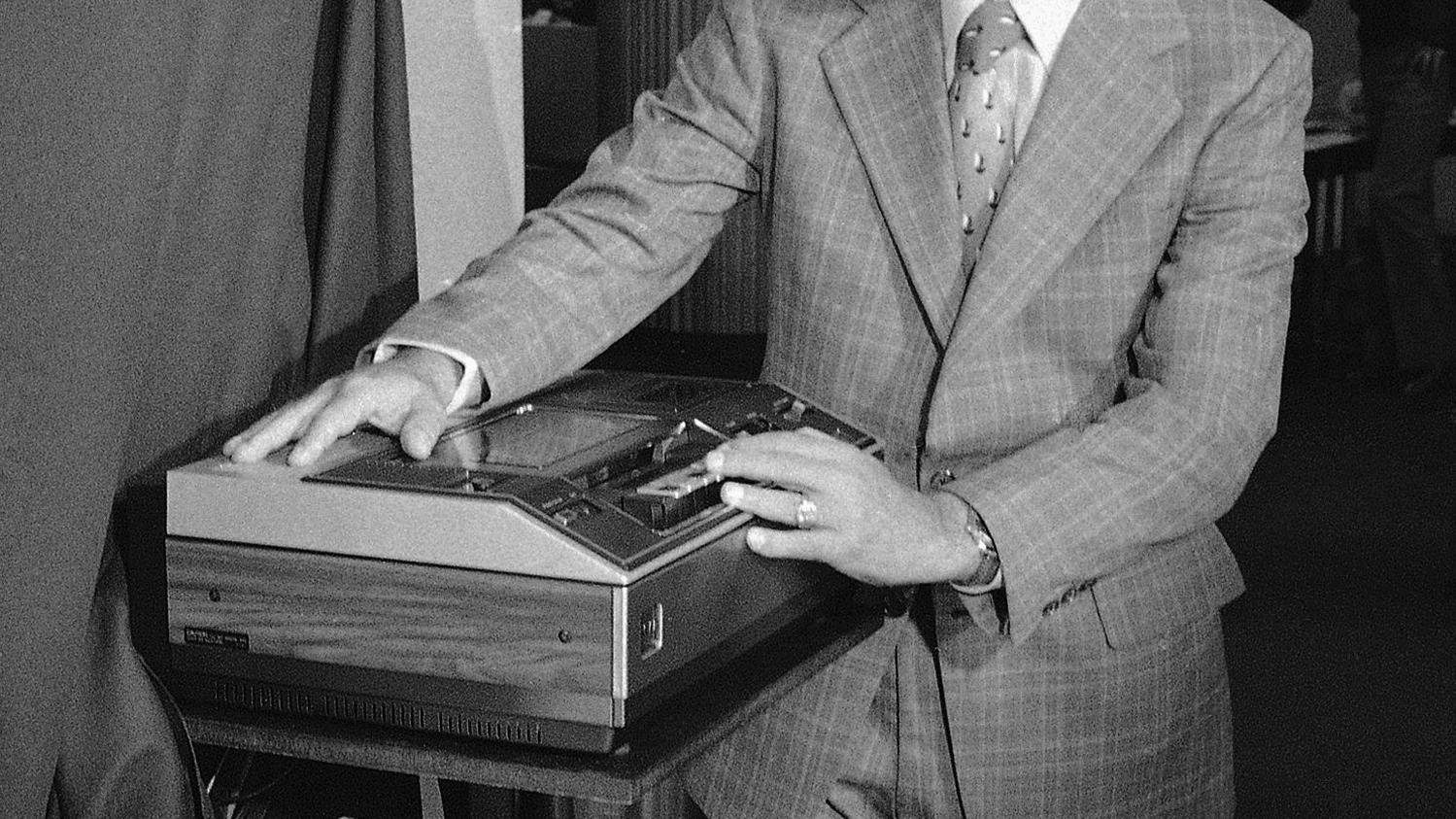 Roy H. Pollack, vice president and general manager of RCA Corporation consumer electronics, demonstrates a new video tape machine Introduced in New York, Aug. 23, 1977. The recorder, intended for home use, will be priced at $1,000, and will be capable of handling cassettes that can record up to four hours of television programs. Cassettes now available record up to two hours. (AP Photo)