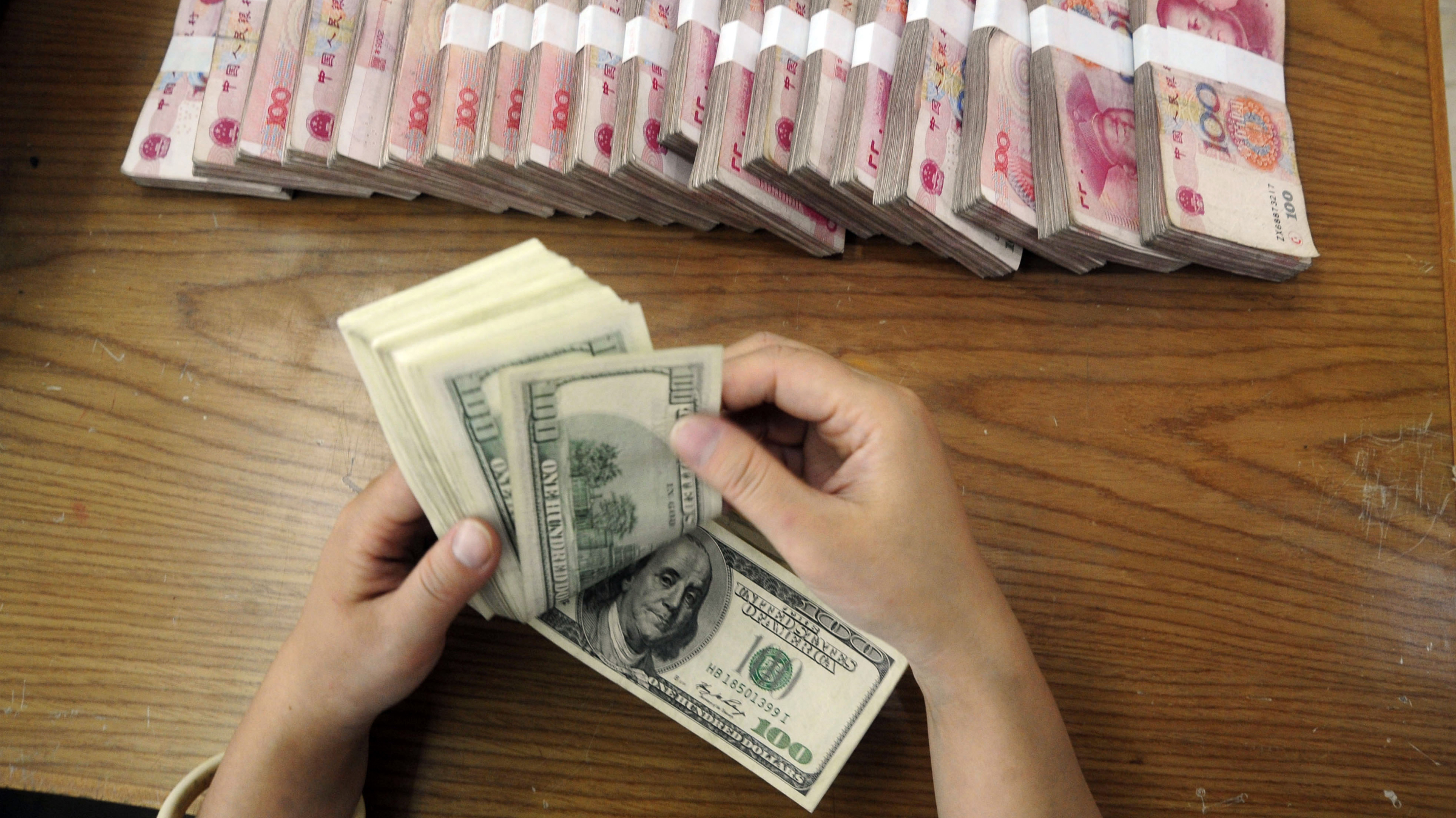 An employee counts U.S. dollar banknotes at a Bank of China branch in Hefei, Anhui province October 16, 2009. China is not manipulating its currency but is piling up foreign exchange reserves at a rate that threatens progress in reducing global economic imbalances, the U.S. Treasury Department said Thursday. REUTERS/Stringer
