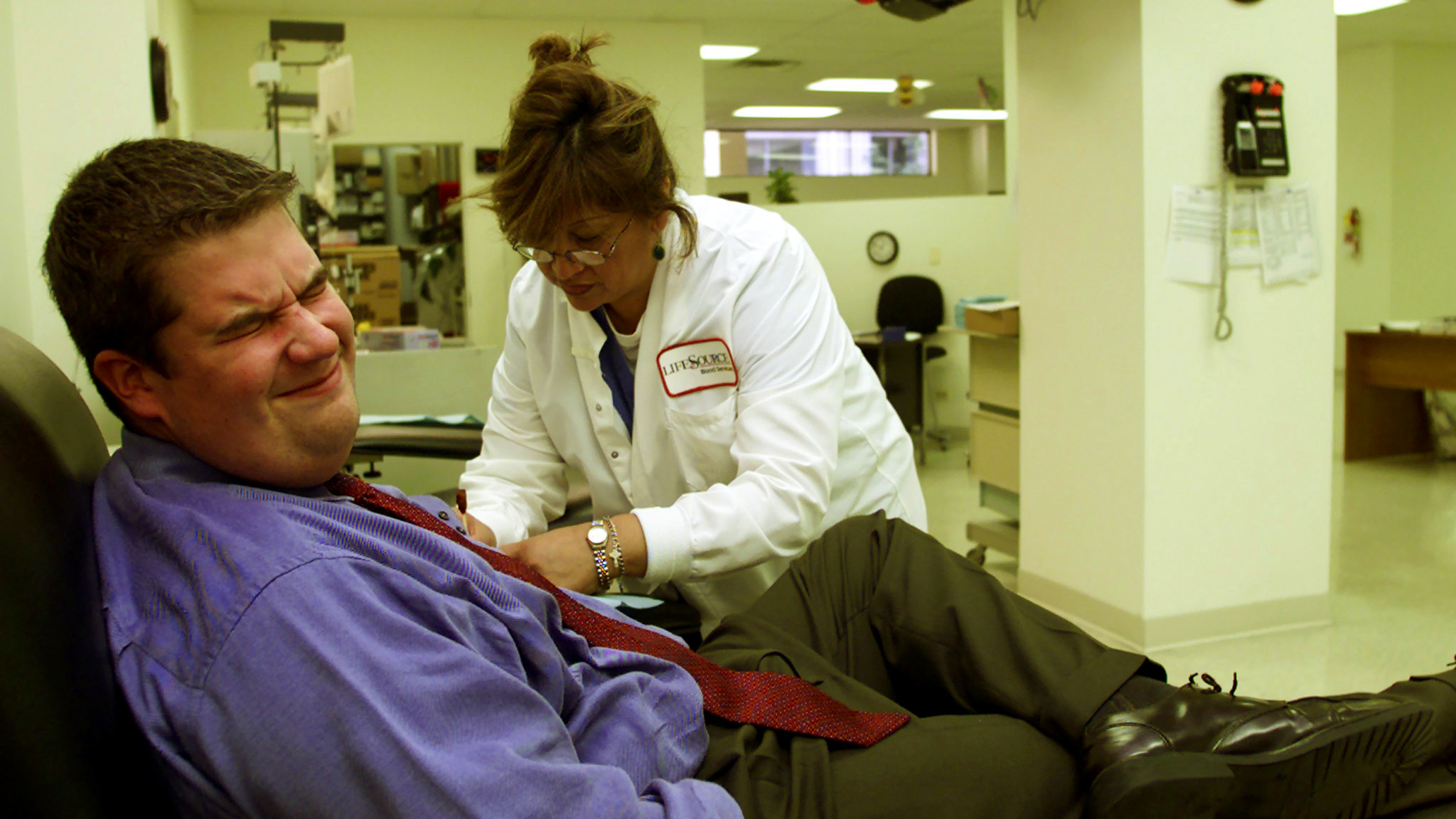 Bob Derboghossian (L) of Chicago, grimaces as phlebotomist Maria Morales (R) inserts a needle to draw blood at Lifesource Blood Center in Chicago, September 12, 2001, as a news program plays on the television in the background, one day after the attack by terrorists on New York City and Washington, D.C. The wait to donate blood was from 2 to 4 hours.