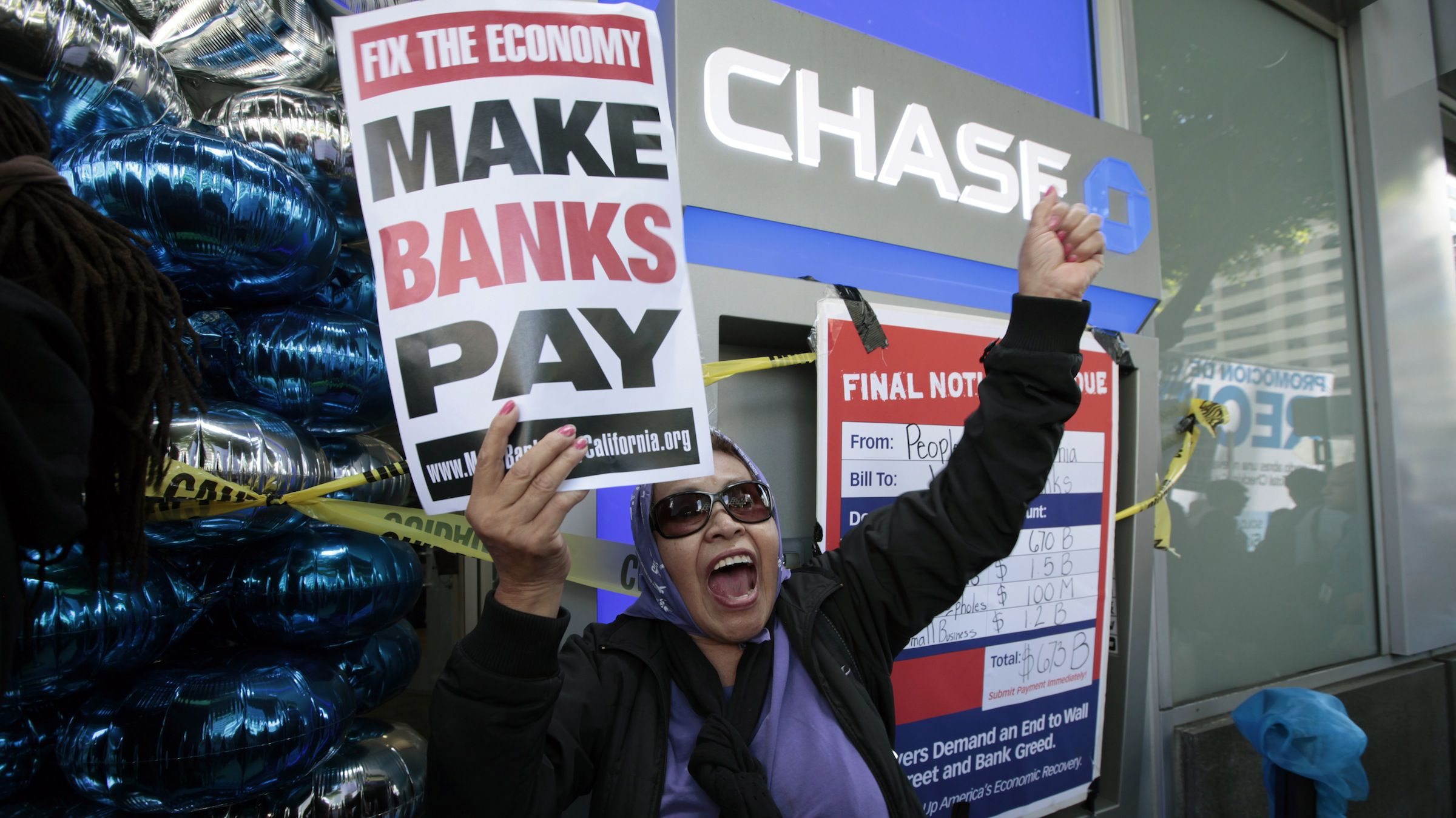 "A woman protests outside a Chase bank branch during a ""Make Wall Street Banks Pay"" protest march in Los Angeles, California October 6, 2011. Los Angeles Police said they arrested eleven people for trespassing at a Bank of America branch. REUTERS/Lucy Nicholson (UNITED STATES - Tags: BUSINESS CIVIL UNREST POLITICS) - RTR2SBFC"
