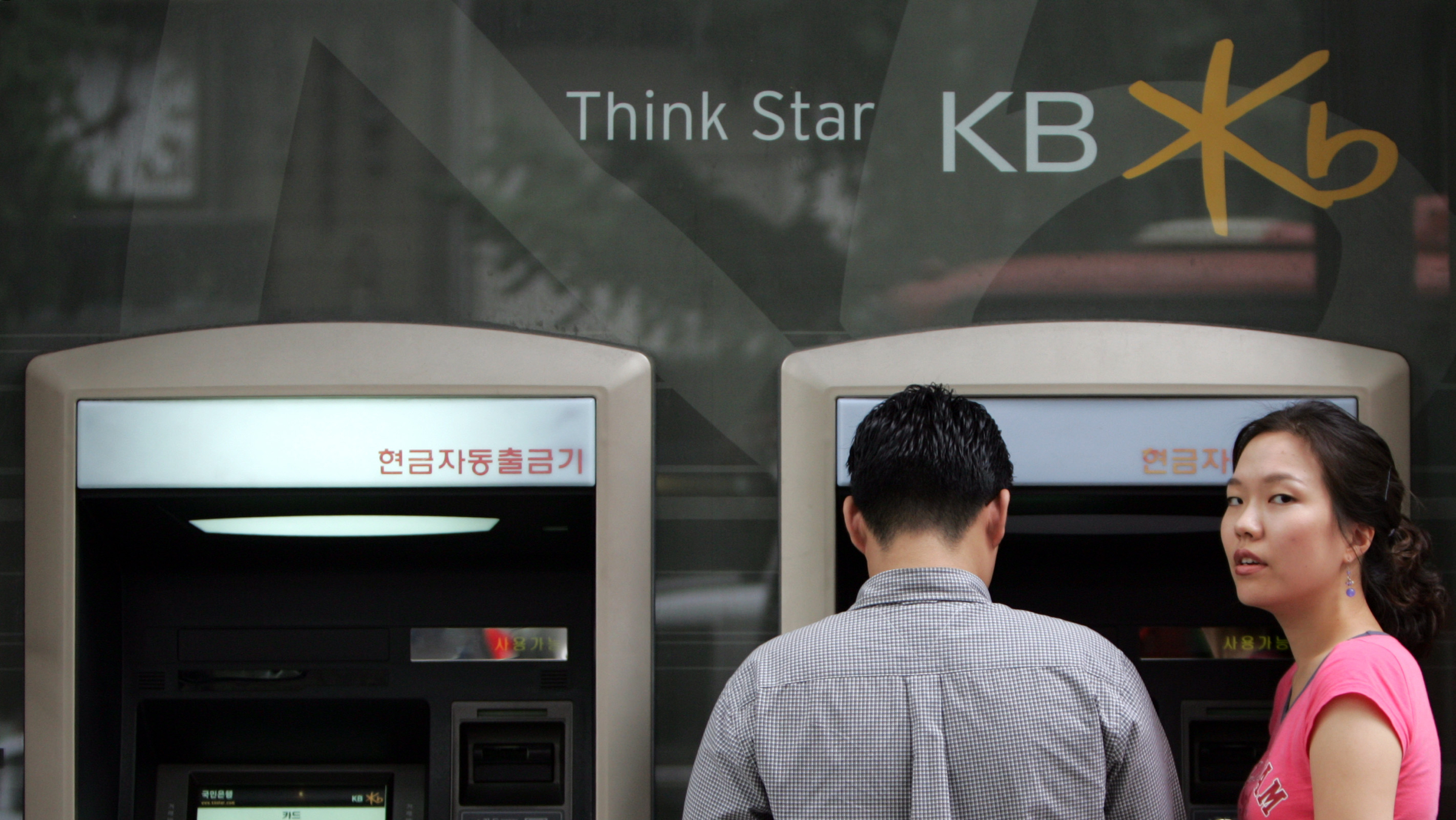South Korean customers use ATMs at Kookmin Bank in Seoul August 26, 2004. South Korea's top financial regulator confirmed on Thursday the chief executive of Kookmin Bank, Kim Jung-tae, would be unable to seek another term due to accounting problems at the country's top lender. REUTERS/Lee Jae-Won  LJW/SH - RTR99X4