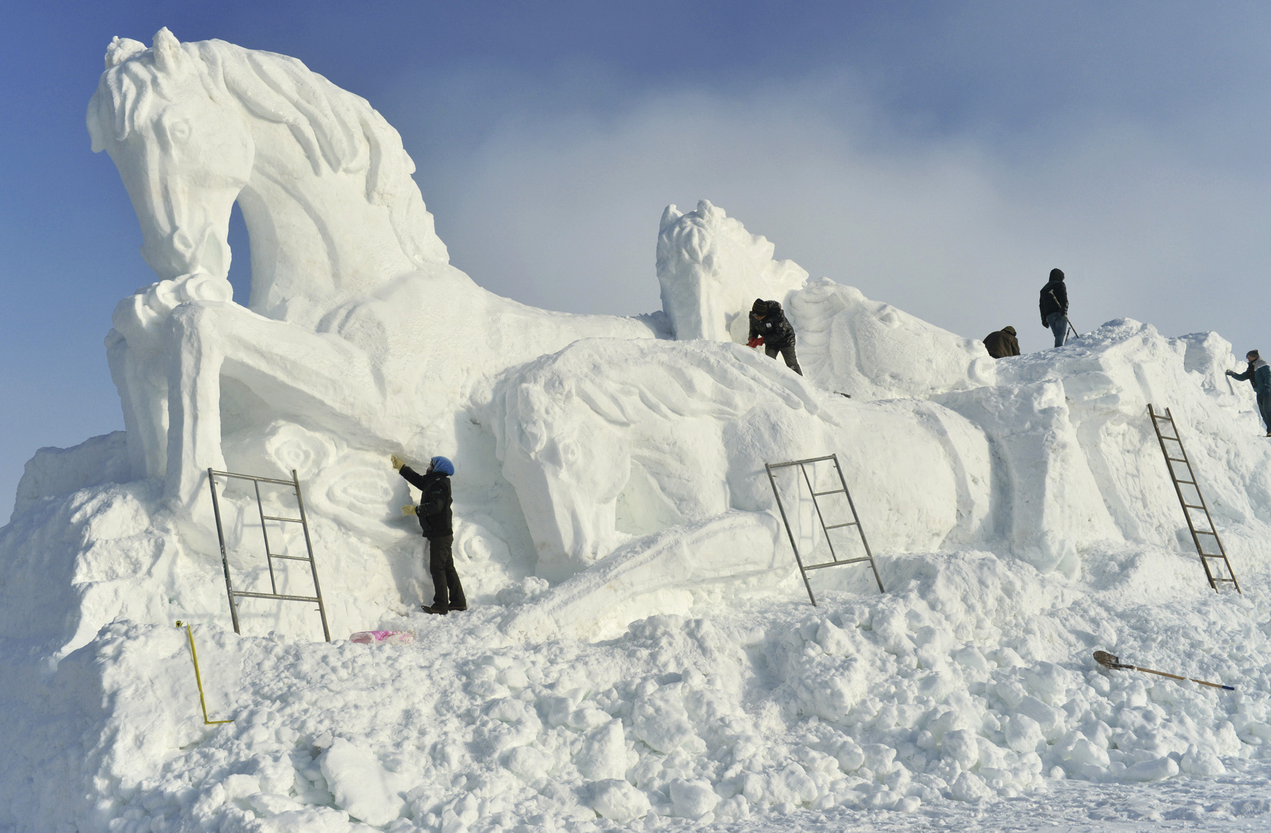 Workers shape a giant snow sculpture of horses ahead of an ice and snow festival in Barkol Kazakh Autonomous County