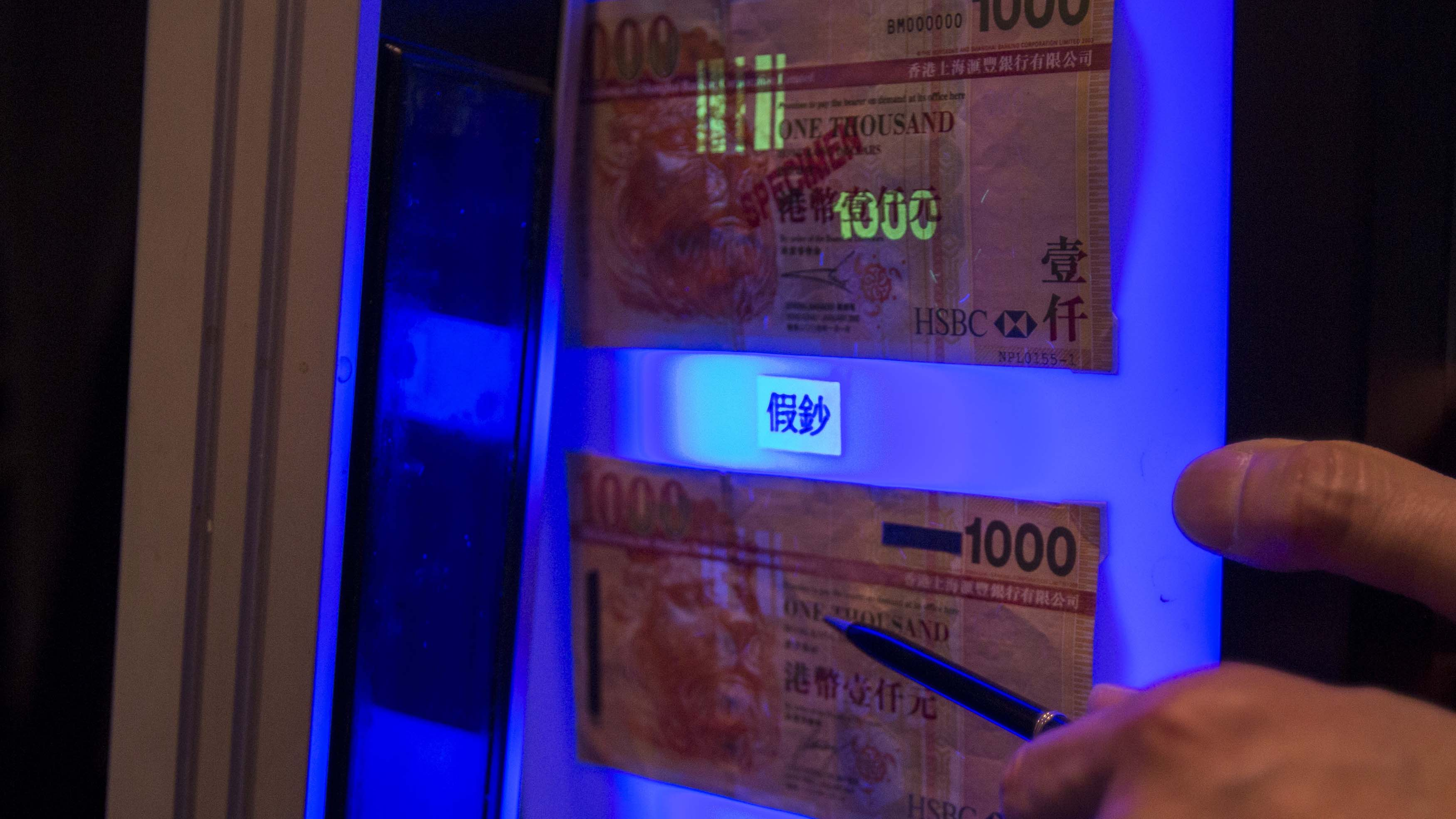 An authentic HK$1,000 ($129) banknote sample is displayed above a counterfeit note under ultraviolet (UV) light during a joint news conference held by Hong Kong Monetary Authority (HKMA) and the Hong Kong Police Force in Hong Kong, December 27, 2013. According to local media, fake HK $1,000 HSBC banknotes were found in Macau on Thursday, a day after counterfeit Bank of China notes were discovered, which leads to a total of 29 fake HK$1,000 notes being found in both Hong Kong and Macau thus far. REUTERS/Tyrone Siu (CHINA - Tags: CRIME LAW BUSINESS) - RTX16UTS