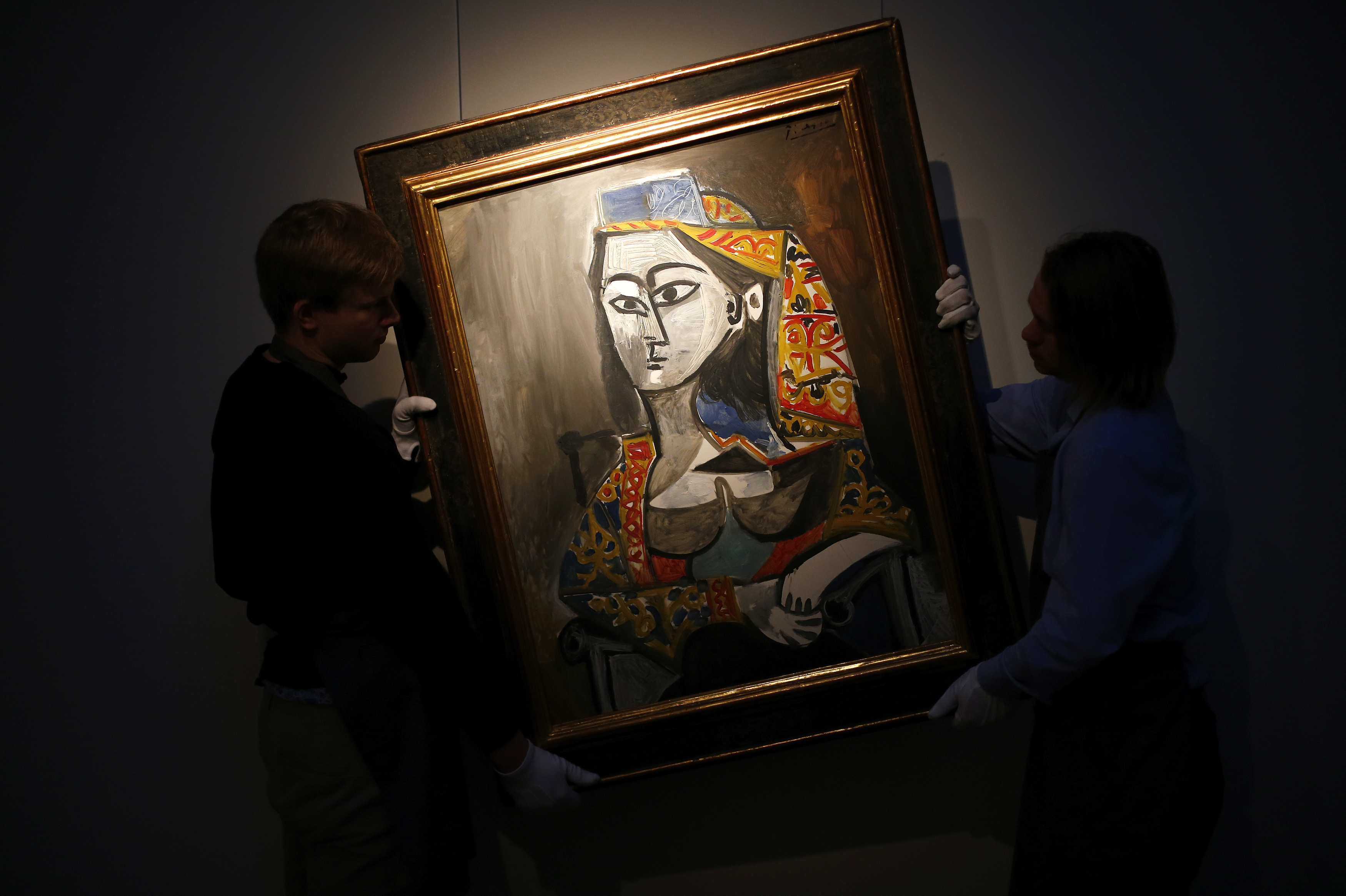 "Workers pose with Pablo Picasso's ""Femme au costume turc dans un fauteuil"", a portrait of his lover Jacqueline Roque painted in 1955, at Christie's auction house in London January 13, 2014. The artwork is expected to fetch 15-20 million GB pounds (U.S. $24.6-32.9 million) when it goes under the hammer at Christie's impressionist and modern art evening sale in London on February 4.  REUTERS/Andrew Winning  (BRITAIN - Tags: ENTERTAINMENT BUSINESS SOCIETY) - RTX17CAN"