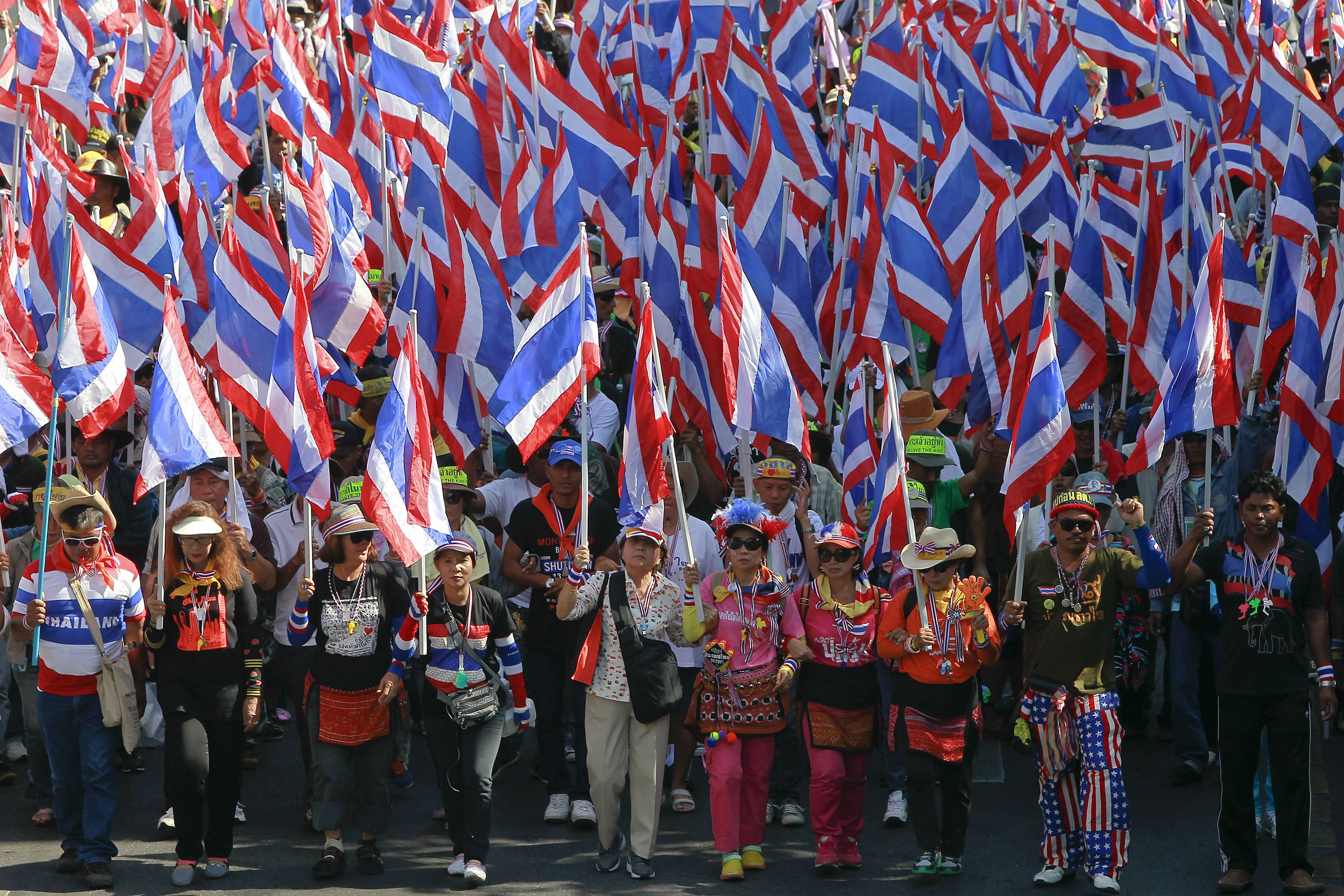 Anti-government protesters carry national flags as they march though central Bangkok January 14, 2014. Protesters trying to topple Thailand's government moved to tighten the blockade around ministries and other state bodies on Tuesday and a hardline faction threatened to storm the stock exchange, while major intersections in the capital Bangkok remained blocked. REUTERS/Chaiwat Subprasom (THAILAND - Tags: CIVIL UNREST POLITICS) - RTX17DH3