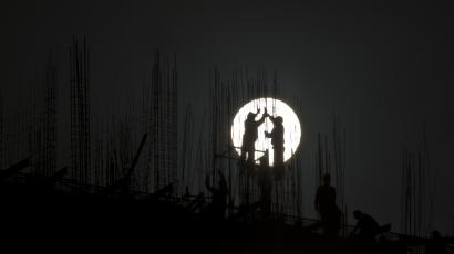 Construction workers install scaffolding on the top of a building during sunset in Shanghai November 11, 2012. China announced on Saturday that it is effectively turning the corner on the economy and likely to meet its growth target for the year, more good news for Communist Party policy makers meeting in Beijing to anoint new leaders for the next decade. REUTERS/Aly Song