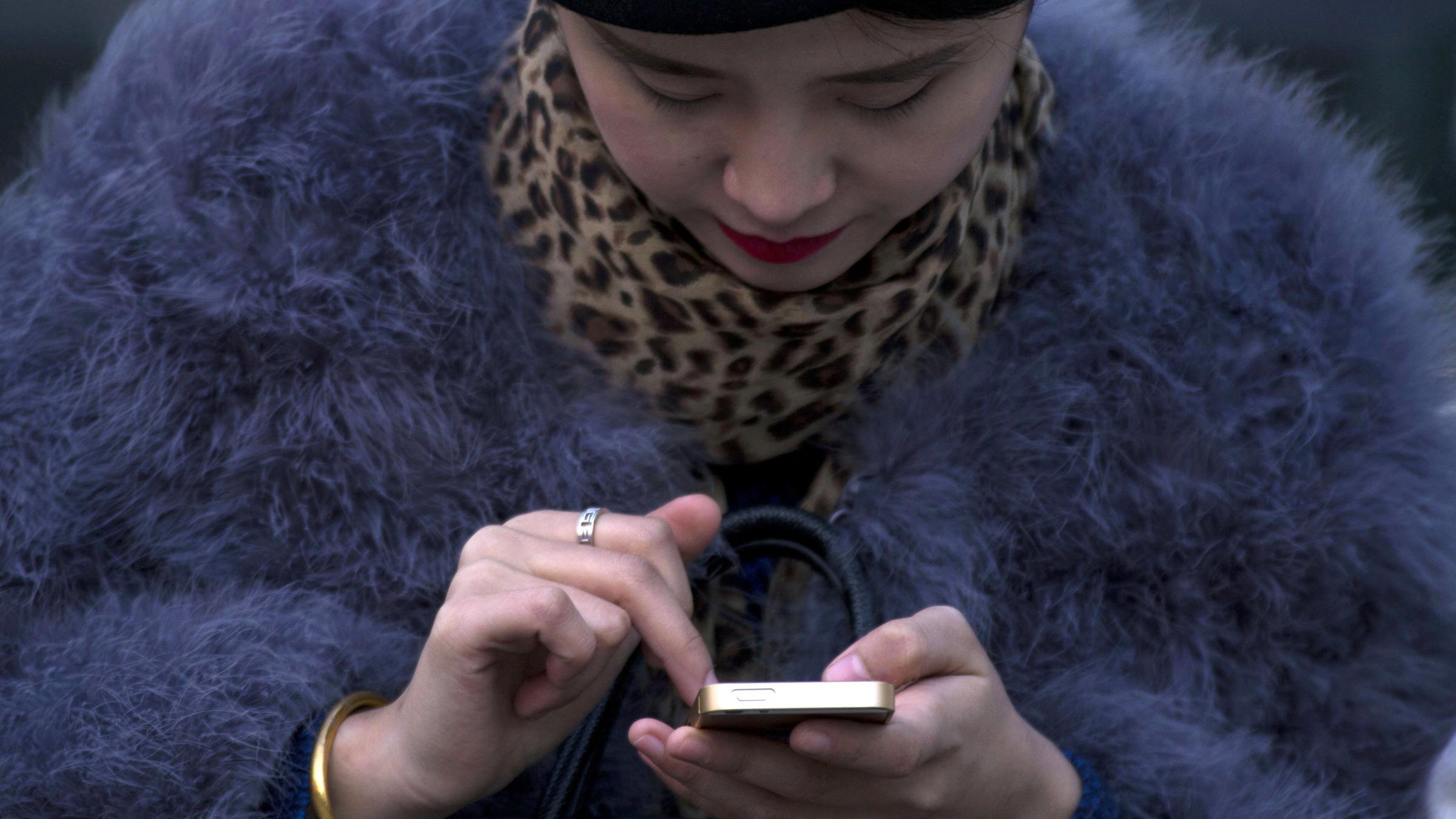 A Chinese woman uses a smartphone in Beijing, China, Sunday, Dec. 1, 2013. (AP Photo/Ng Han Guan)