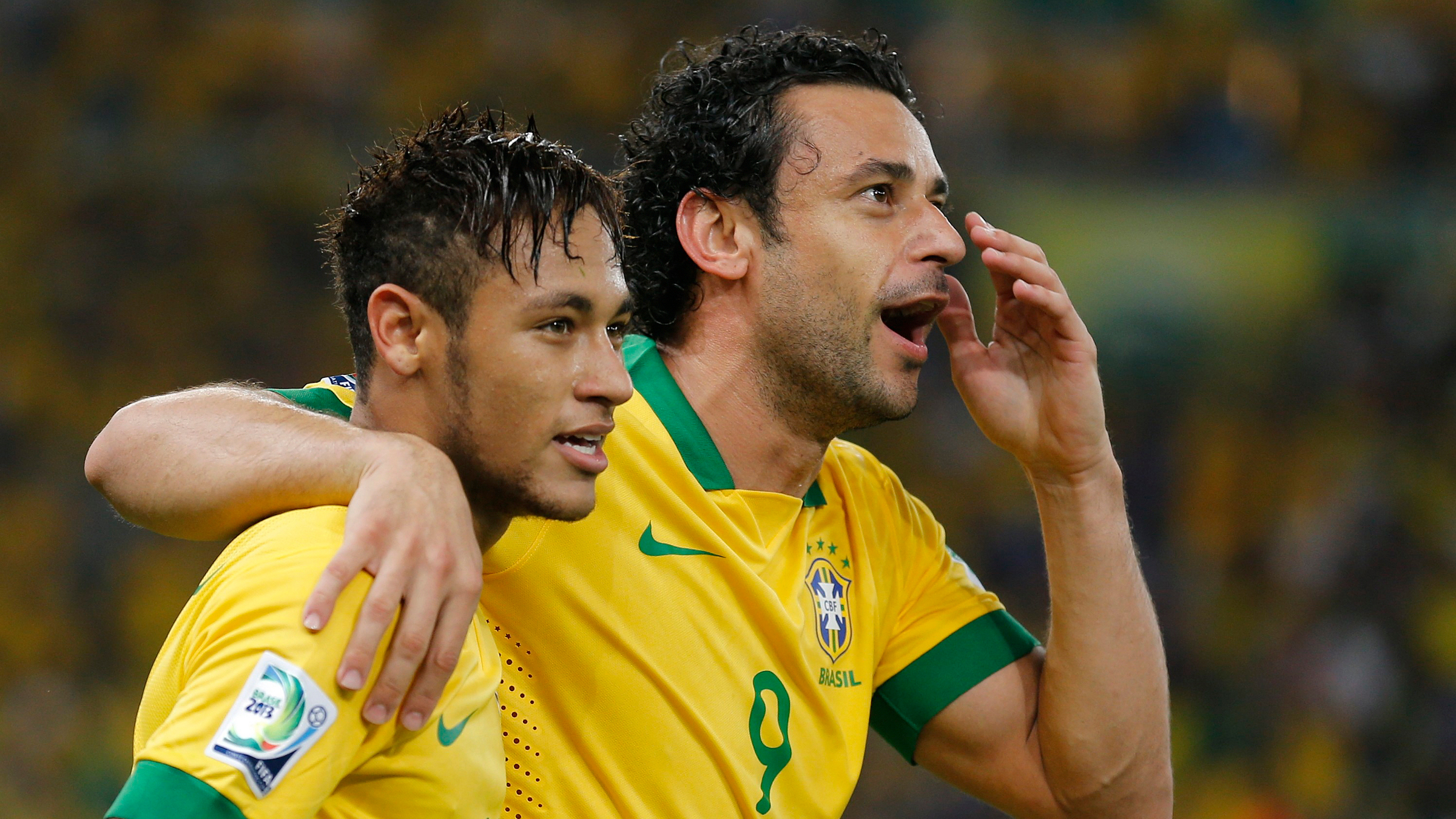 Brazil's Fred (R) celebrates with teammate Neymar after scoring a second half goal against Spain during the Confederations Cup final soccer match at the Estadio Maracana in Rio de Janeiro June 30, 2013.
