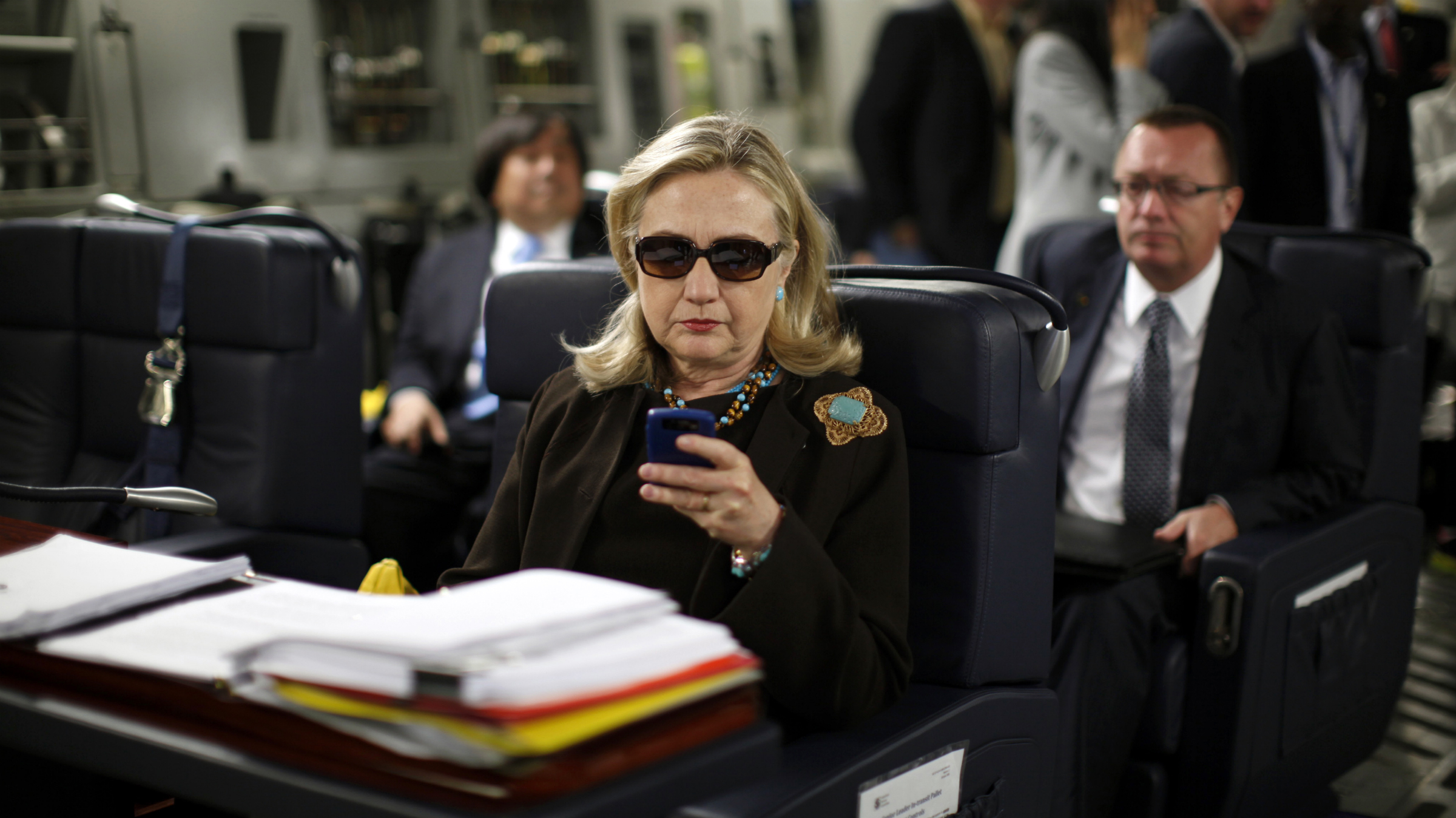 Hillary Clinton using her phone on a plane.