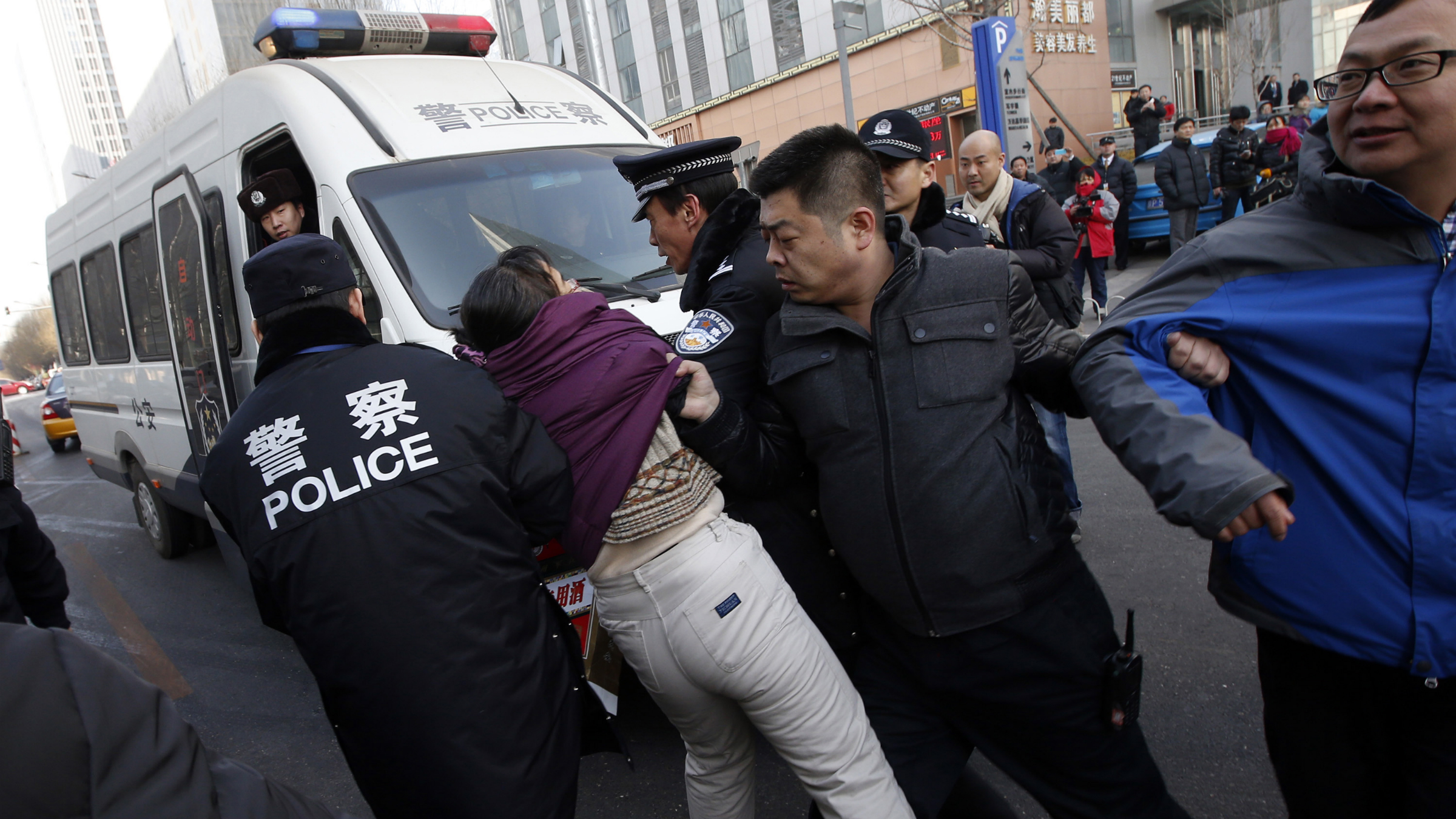 "Liu Chunxia, a supporter of Xu Zhiyong, one of China's most prominent rights advocates, is detained by policemen while she gathers with other supporters nearby a court where Xu's trial is being held in Beijing January 22, 2014. When dozens of activists unfurled banners across the country last March and April calling for officials to disclose their assets, they did so at the urging of one of China's most prominent rights advocates, Xu Zhiyong. Xu, 40, stands trial on Wednesday on a charge of ""gathering a crowd to disturb public order"" punishable by up to five years in prison. His case will almost certainly spark fresh criticism from Western governments over Beijing's crackdown on dissent. REUTERS/Kim Kyung-Hoon"