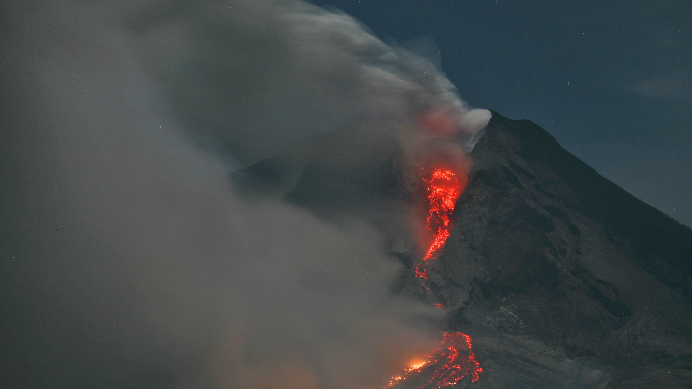 Mount Sinabung erupts with molten rocks and hot gasses as seen from  Jeraya, North Sumatra, Indonesia, early Tuesday, Jan. 14, 2014. The volcano has sporadically erupted since September, forcing thousands of people who live around it slopes to flee their homes. (AP Photo/Binsar Bakkara)