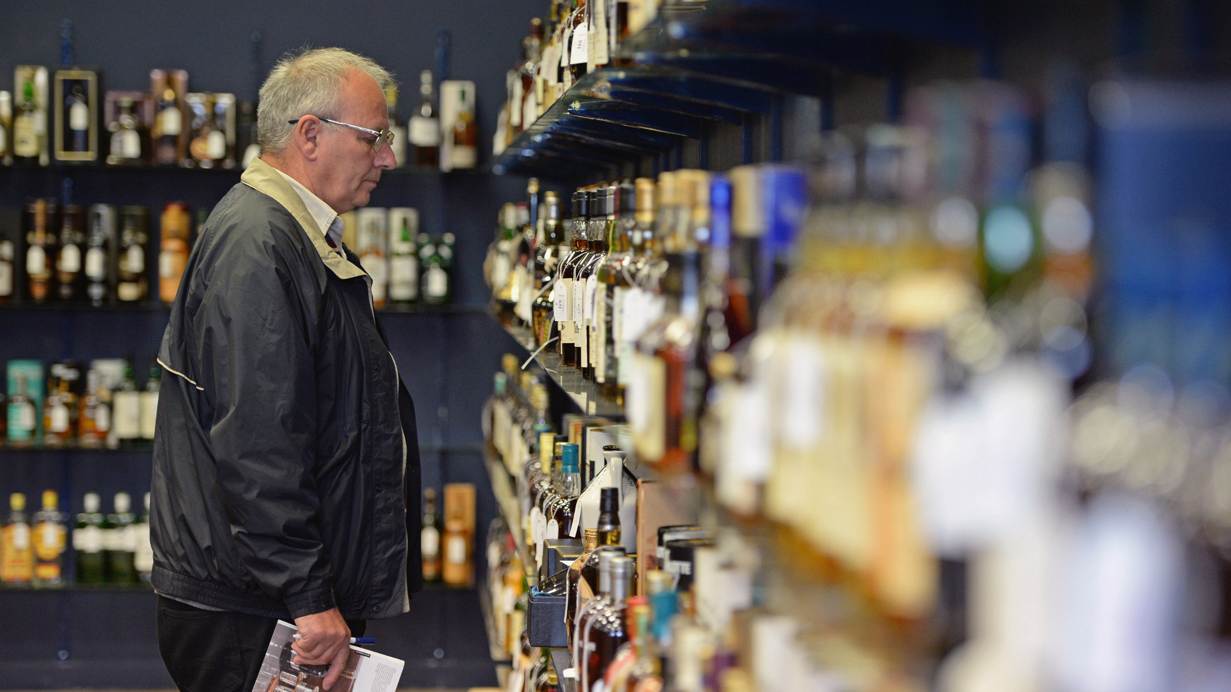 GLASGOW, SCOTLAND - SEPTEMBER 04:  A collector views whiskies going on sale today at McTears Auctioneers on September 4, 2013 in Glasgow,Scotland. Whiskey collectors as far afield as the United States, China and Australia will be looking in on the auction as some of the world's rarest whiskies go under the hammer.  (Photo by Jeff J Mitchell/Getty Images)