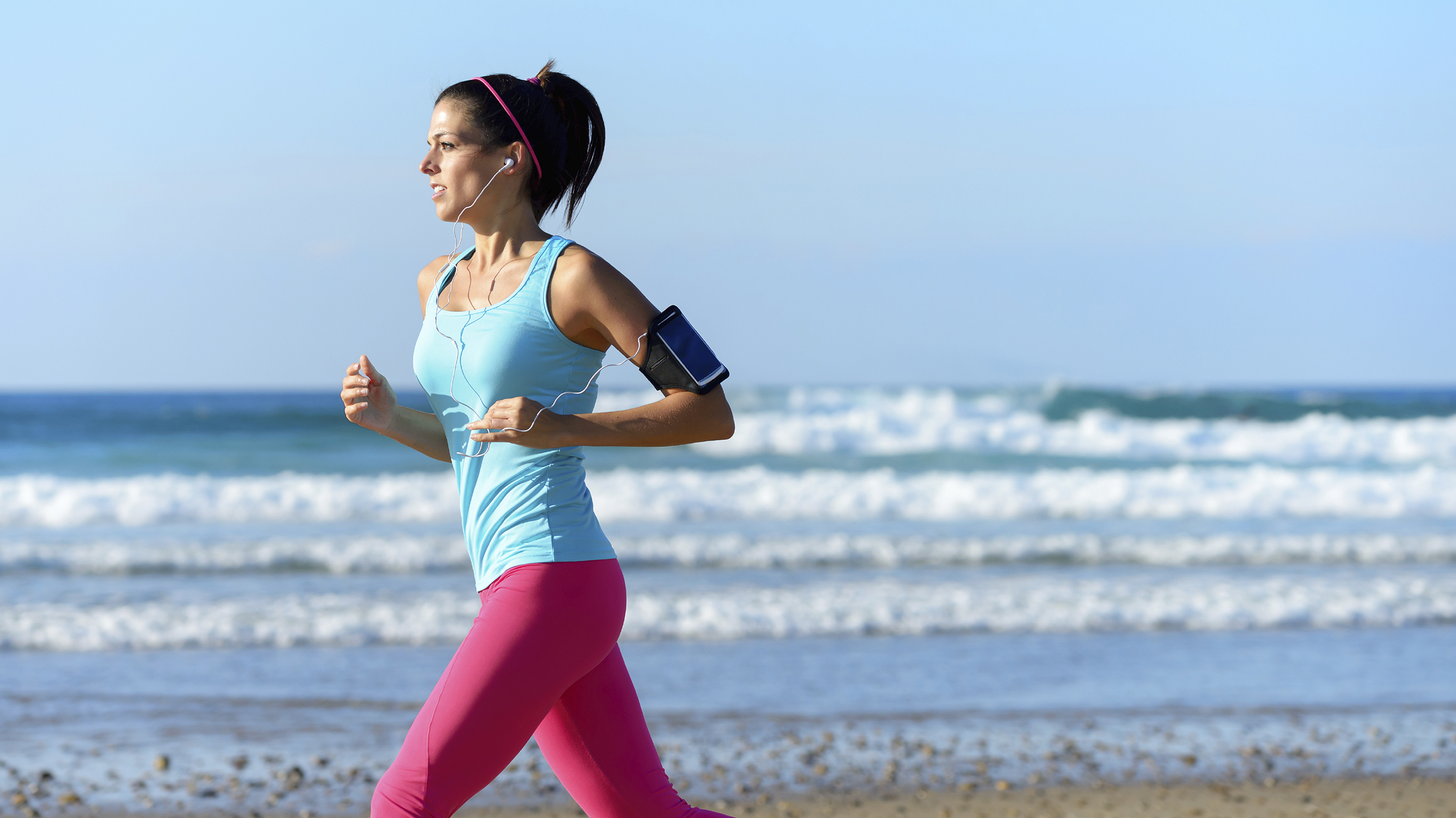 Fitness woman on running workout at the beach on summer. Sporty girl wearing earphones and sport armband for listening smartphone music. Female healthy athlete training outdoors on sea background.