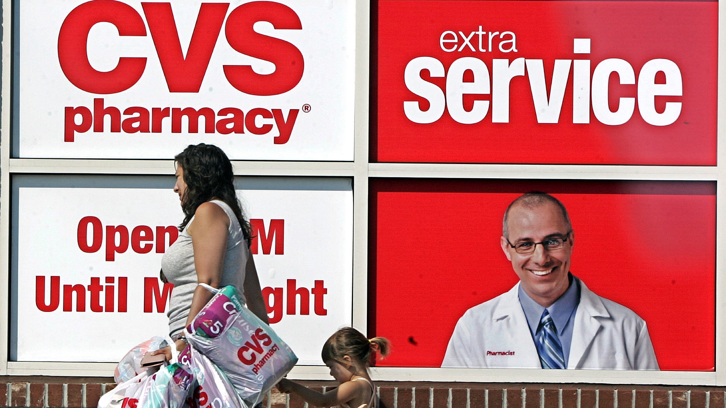 ** FILE ** CVS posters are seen in front of a CVS store in Boston, in this Aug. 3, 2006 file photo. CVS Caremark Corp., one of the nation's biggest drugstore chains, on Thursday, Nov. 1, 2007 said its third-quarter profit more than doubled due to an 83 percent sales gain and the use of more generic drugs. (AP Photo/Chitose Suzuki, file)