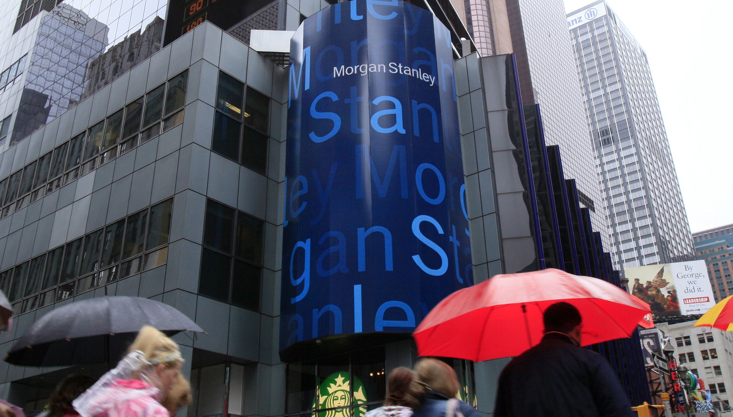 """People walk by Morgan Stanley headquarters in New York's Times Square, Monday, May 21, 2012. Although many investors had hoped for a big first-day pop, Facebook's stock opened Friday at $42.05 and fluctuated between $45 and $38 throughout the day before closing at $38.23. Wedbush analyst Michael Pachter, who came out with an """"Outperform"""" rating on Facebook before its IPO, said he thinks the investment banks that arranged the offering overestimated demand for the company's stock. Last week, the bankers, led by Morgan Stanley, increased the offering price range. (AP Photo/Richard Drew)"""