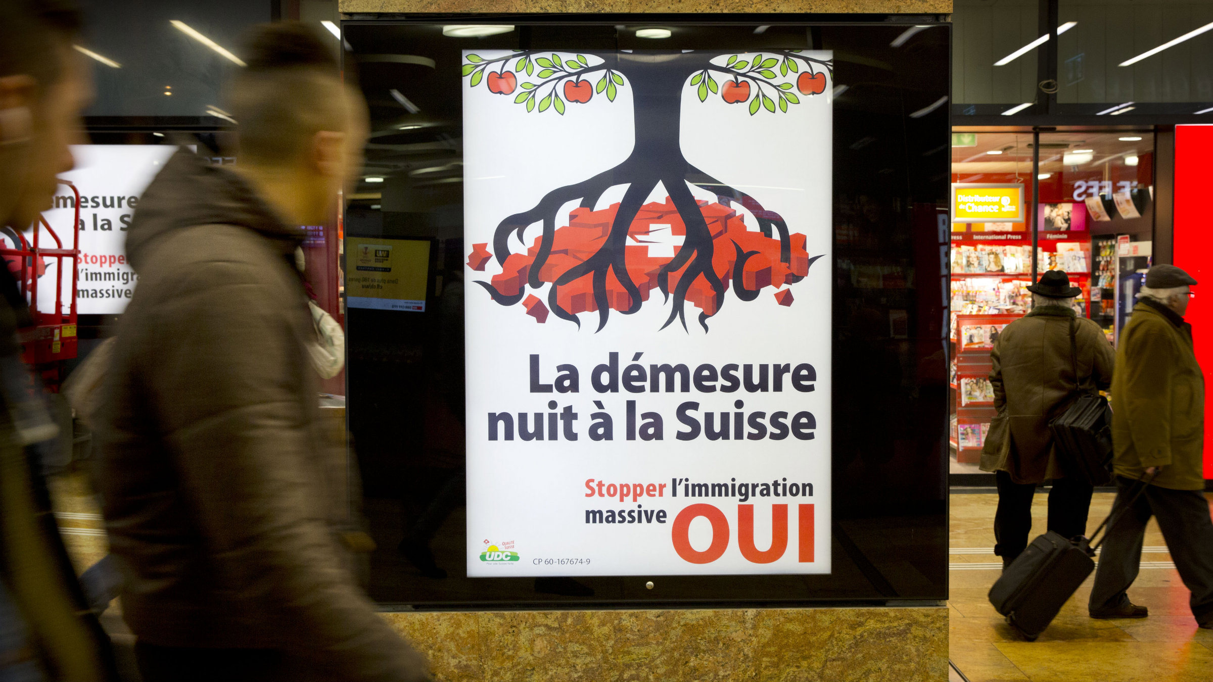 """Pedestrians in Geneva pass a poster in favor of the """"stop mass immigration"""" initiative. AP Photo/Anja Niedringhaus"""